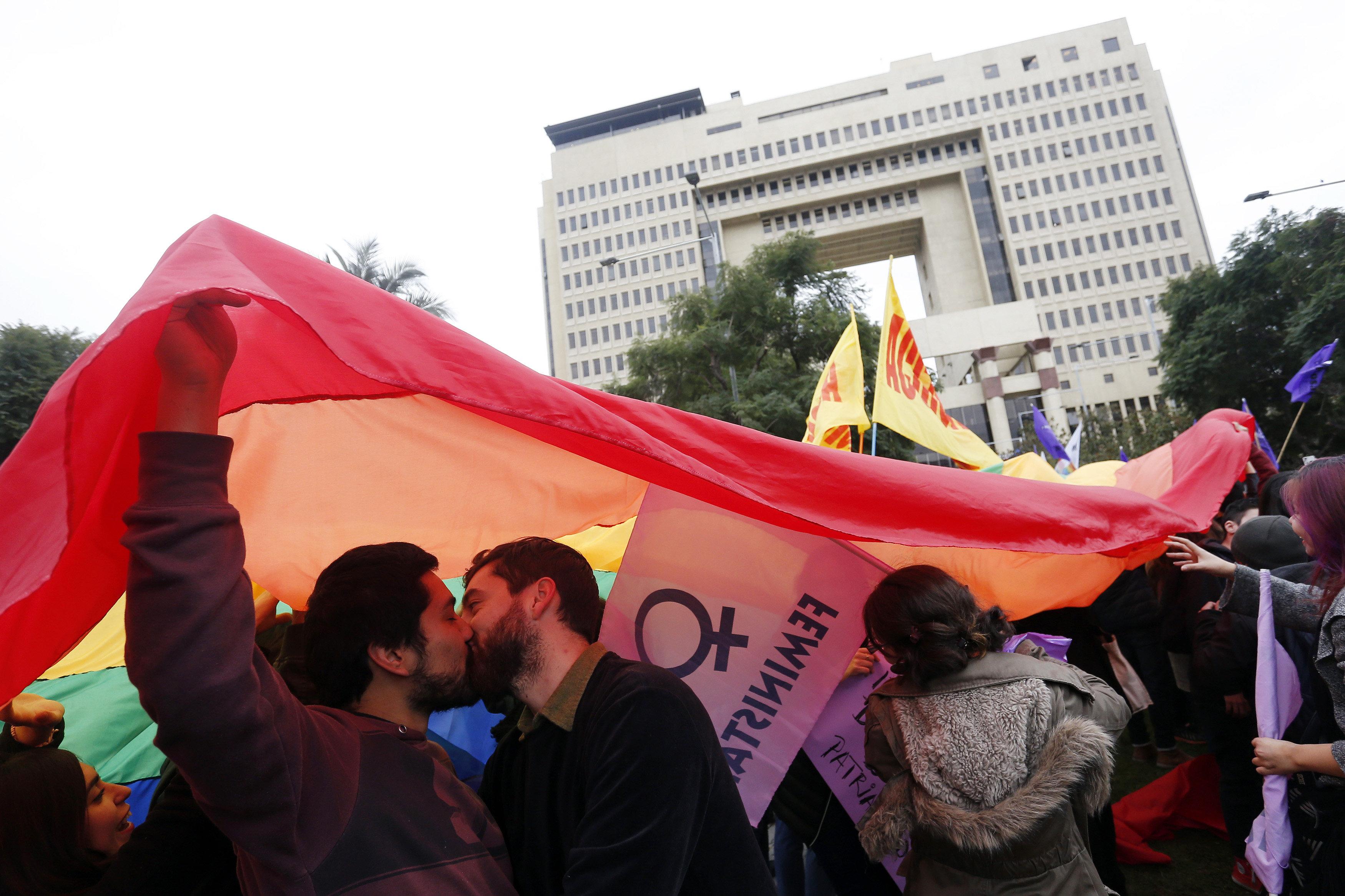 """Parelles es besen sota una bandera LGBTI com a senyal de protesta pel pas del denominat """"Bus de la Llibertat"""" davant del Congrés Nacional de Valparaíso (Xile). /RAÚL ZAMORA"""