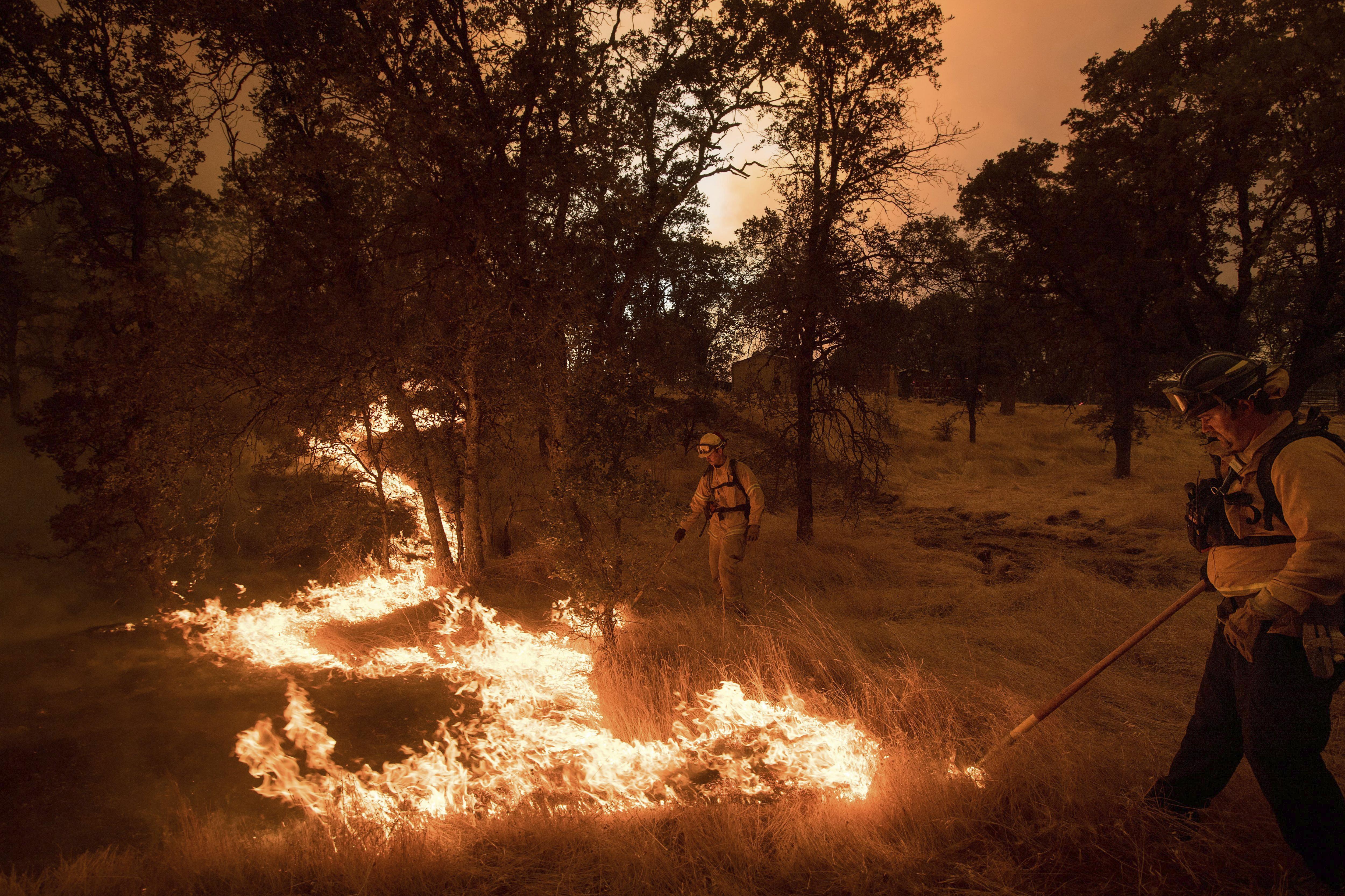 Dos bombers cremen vegetació per crear un tallafoc al costat d'un habitatge amenaçat per les flames a Califòrnia (Estats Units). /NOAH BERGER