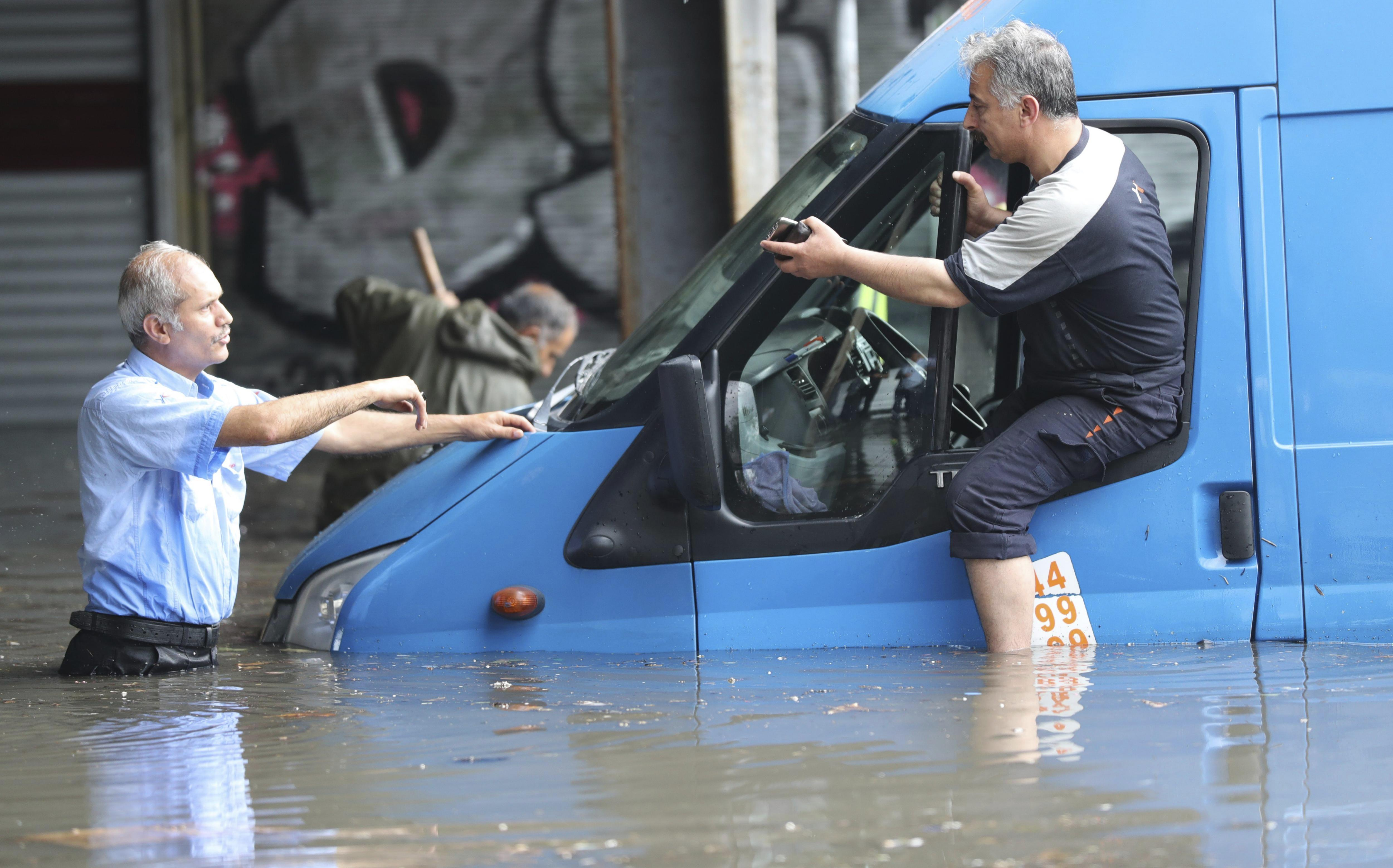 Dos homes intenten treure un cotxe d'una carretera negada per les fortes pluges caigudes en les darreres hores a Turquia. /TOLGA BOZOGLU