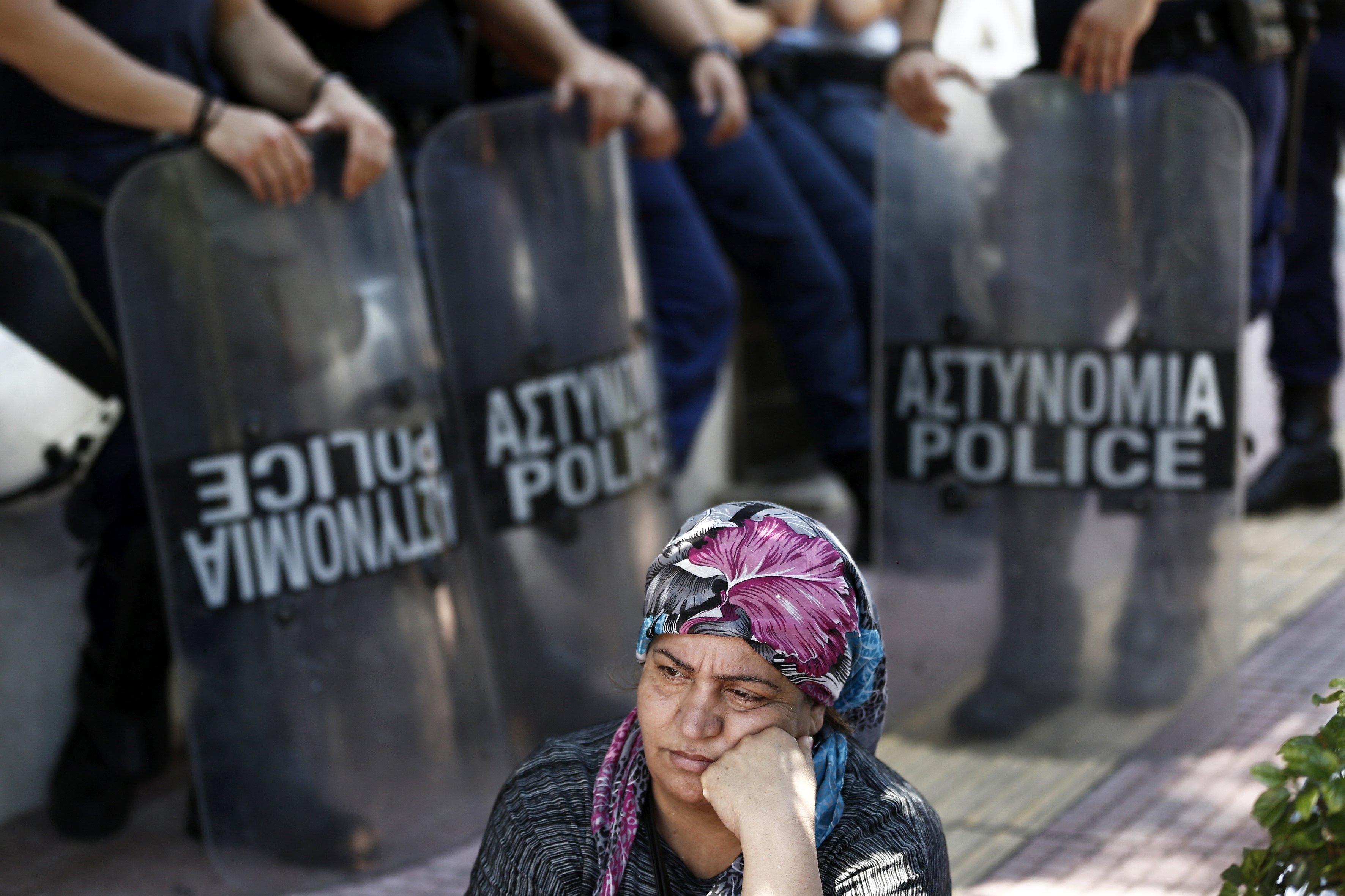 Diversos refugiats sirians protesten a l'entrada de l'Ambaixada alemanya d'Atenes (Grècia). /YANNIS KOLESIDIS