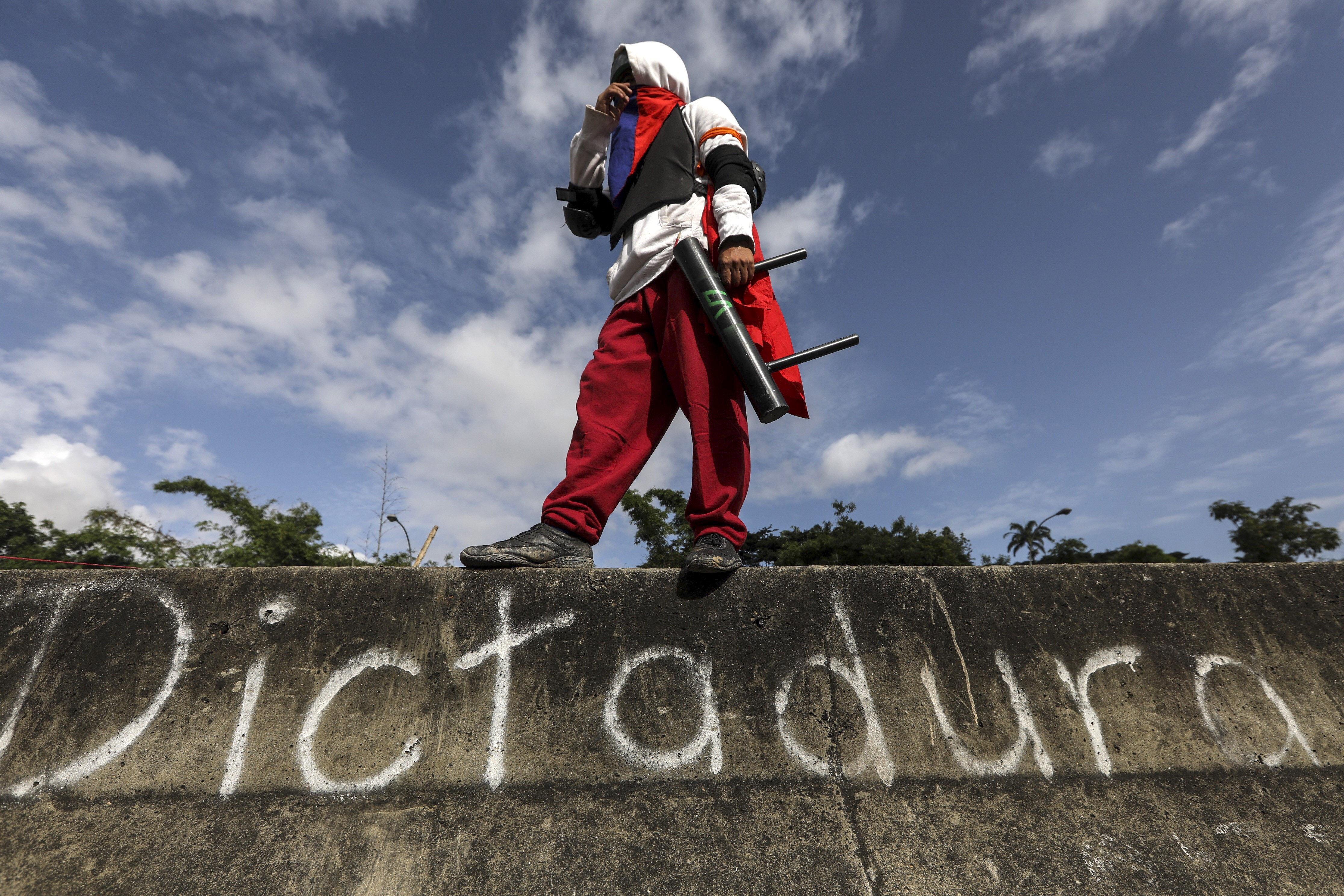 Un manifestant encaputxat participa en la vaga general convocada per l'oposició a Caracas (Veneçuela). /MIGUEL GUTIÉRREZ