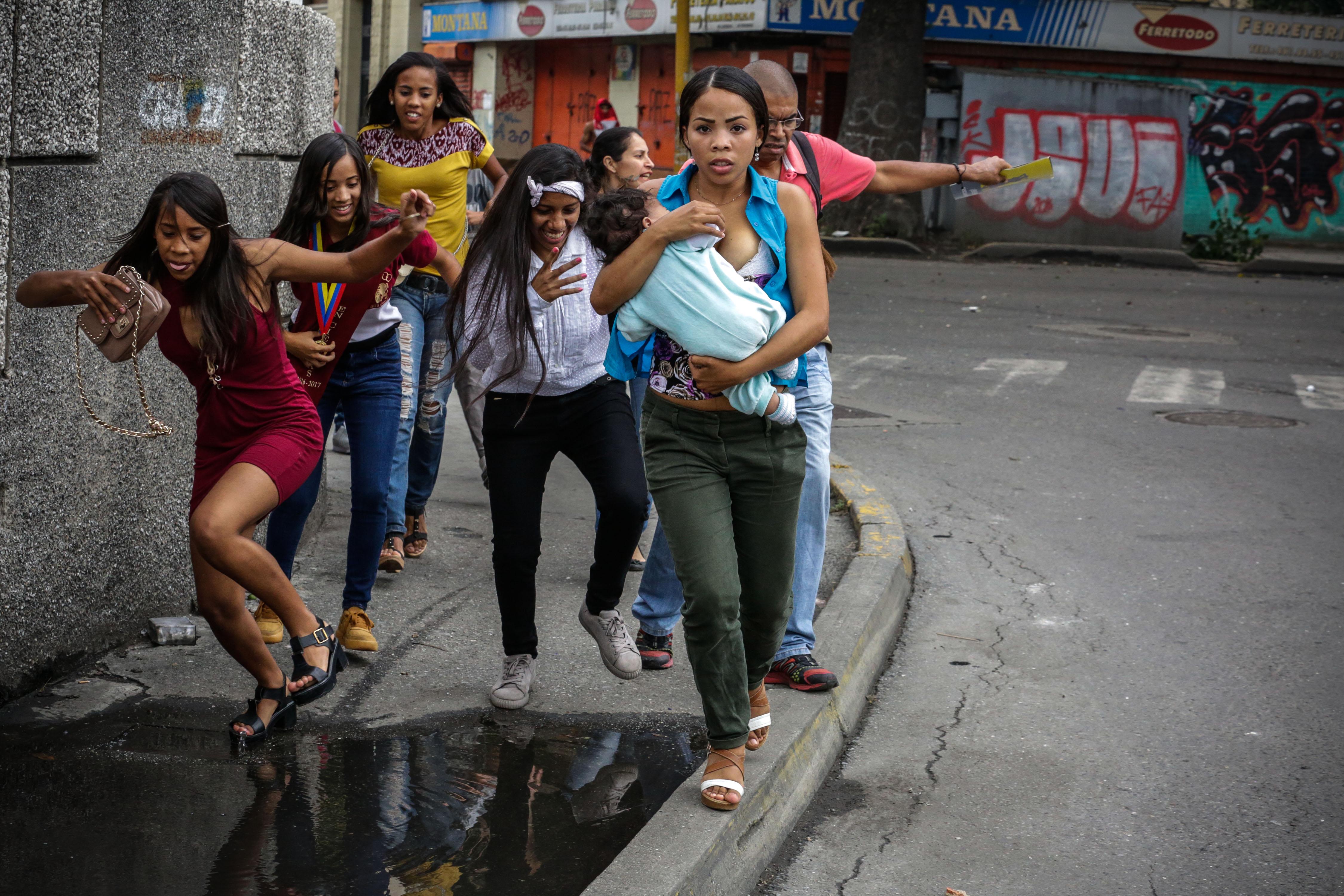 Ciutadans tracten d'evitar els xocs entre manifestants opositors i agents de la Guàrdia Nacional Bolivariana (GNB) a Caracas (Veneçuela). /CRISTIAN HERNÁNDEZ