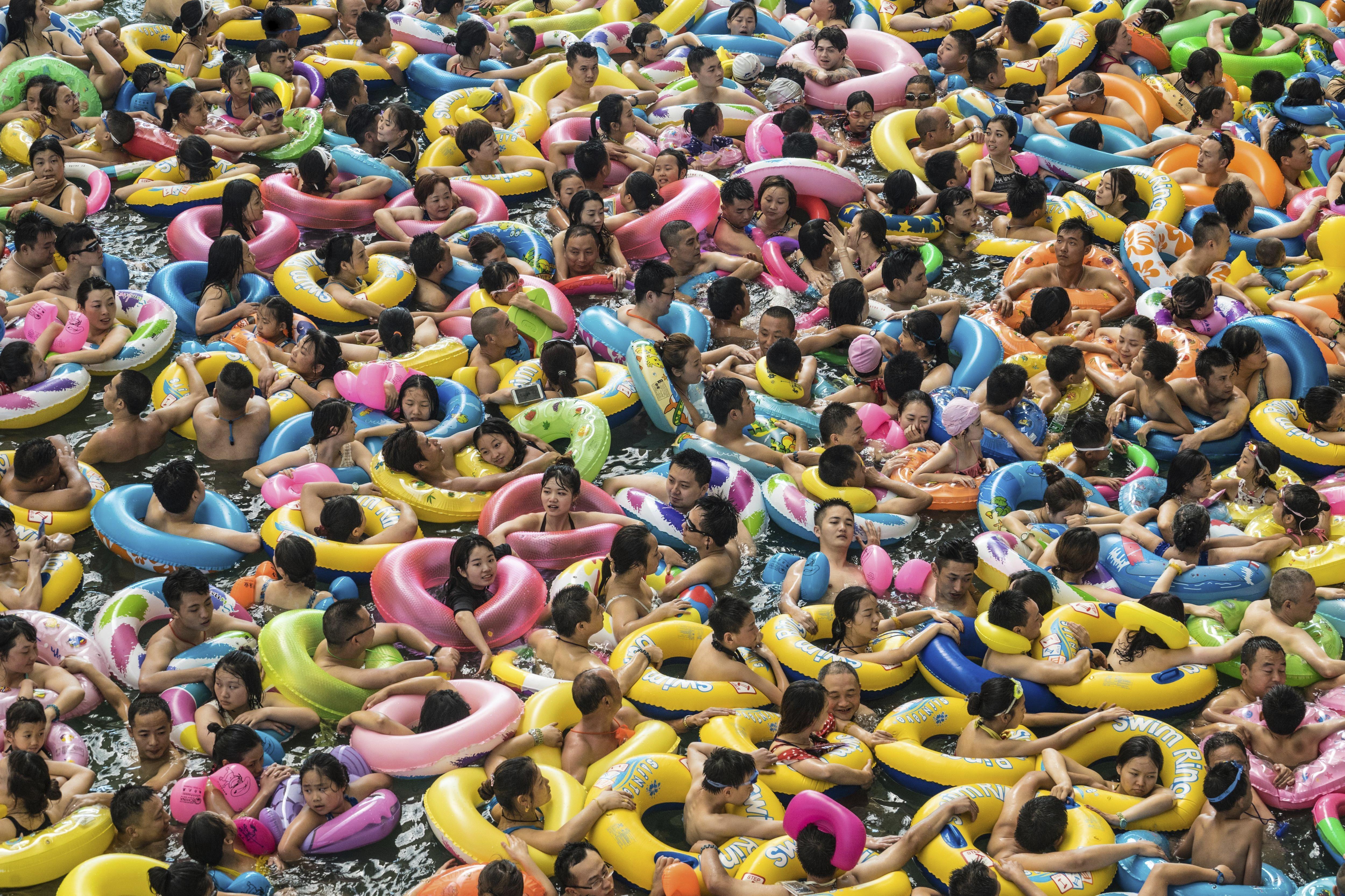 """Turistes xinesos es donen un bany en el llac anomenat """"Mar Mort de Xina"""" a Suining. /LOLA LEVAN"""