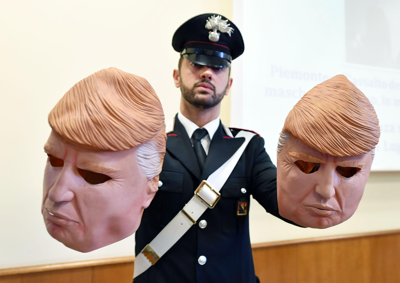 Un membre dels Carabinari mostra unes màscares amb la imatge del president dels Estats Units, Donald Trump, usades per dos lladres, durant una roda de premsa a Turín, Itàlia. /ALESSANDRO DI MARCO