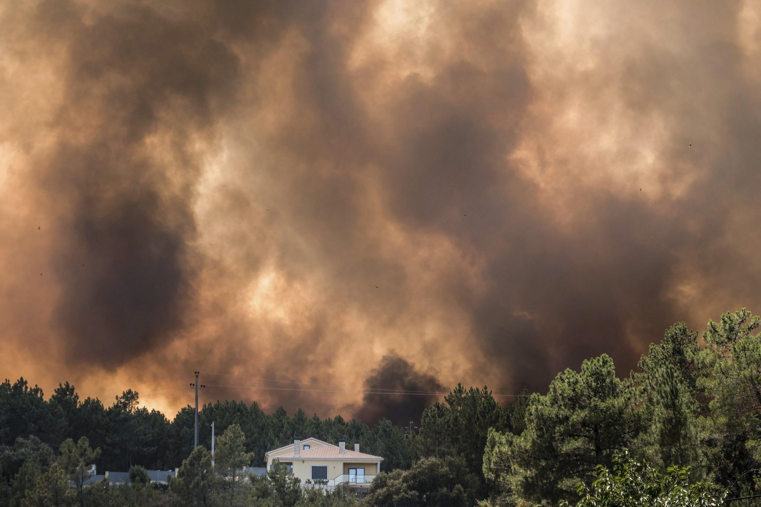 Vista de les flames i el fum prop d'un habitatge en un incendi forestal a Portugal. /SERGIO AZENHA