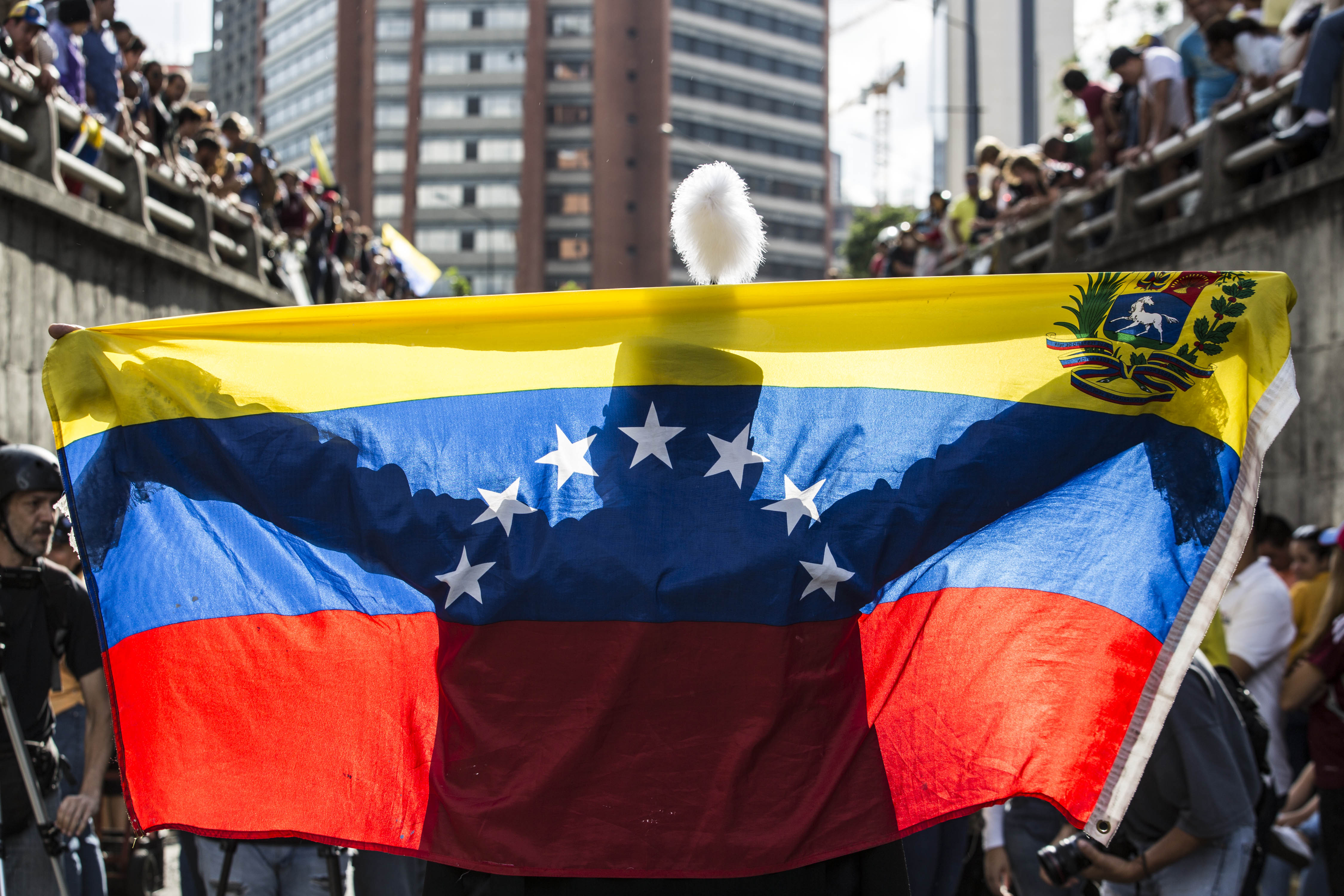 Una persona estén una bandera veneçolana davant desenes de manifestants durant una protesta antigovernamental. /NATHALIE SAYAG