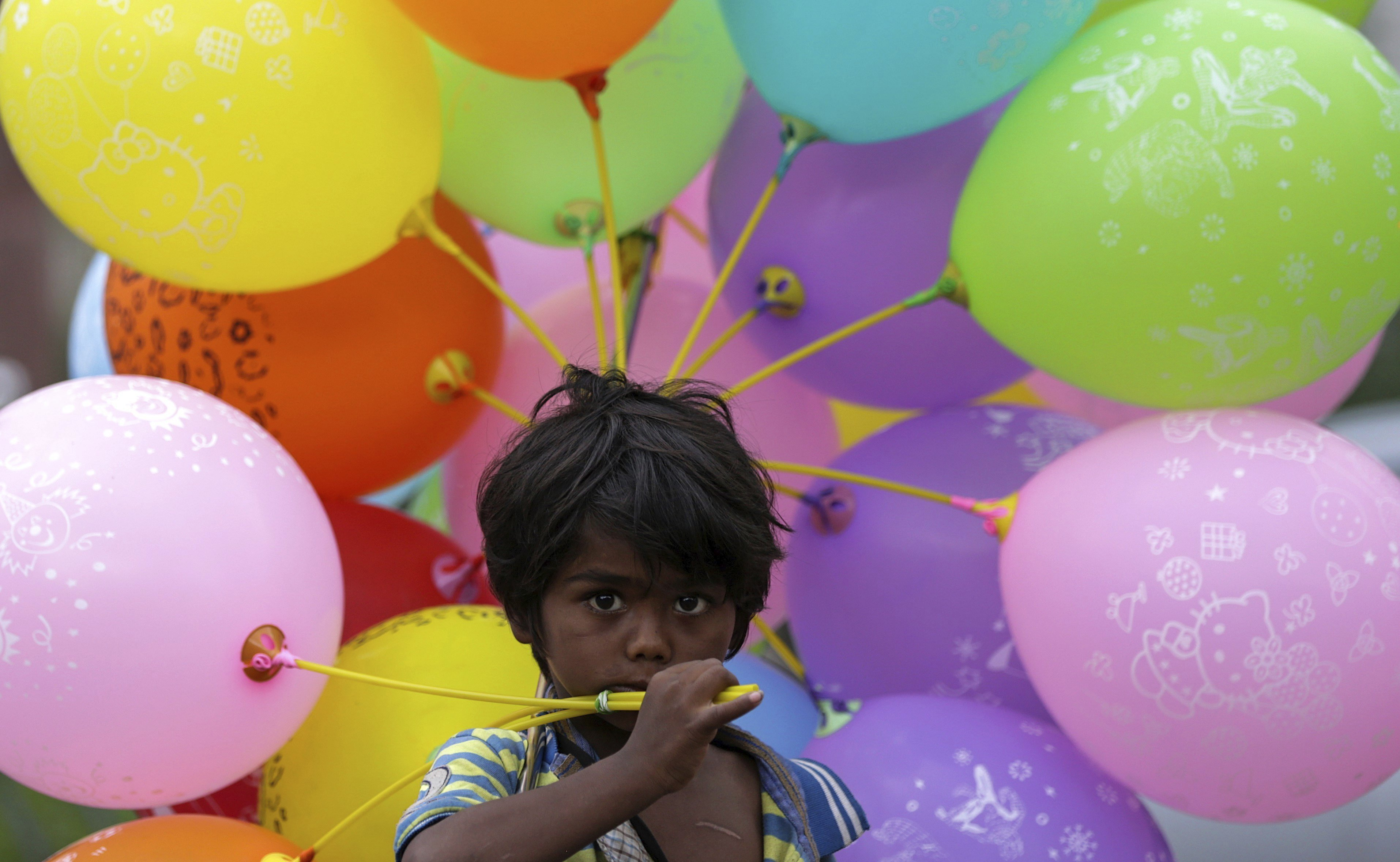 Un nin de sis anys ven globus en un carrer de Bombai, Índia. /DIVYAKANT SOLANKI