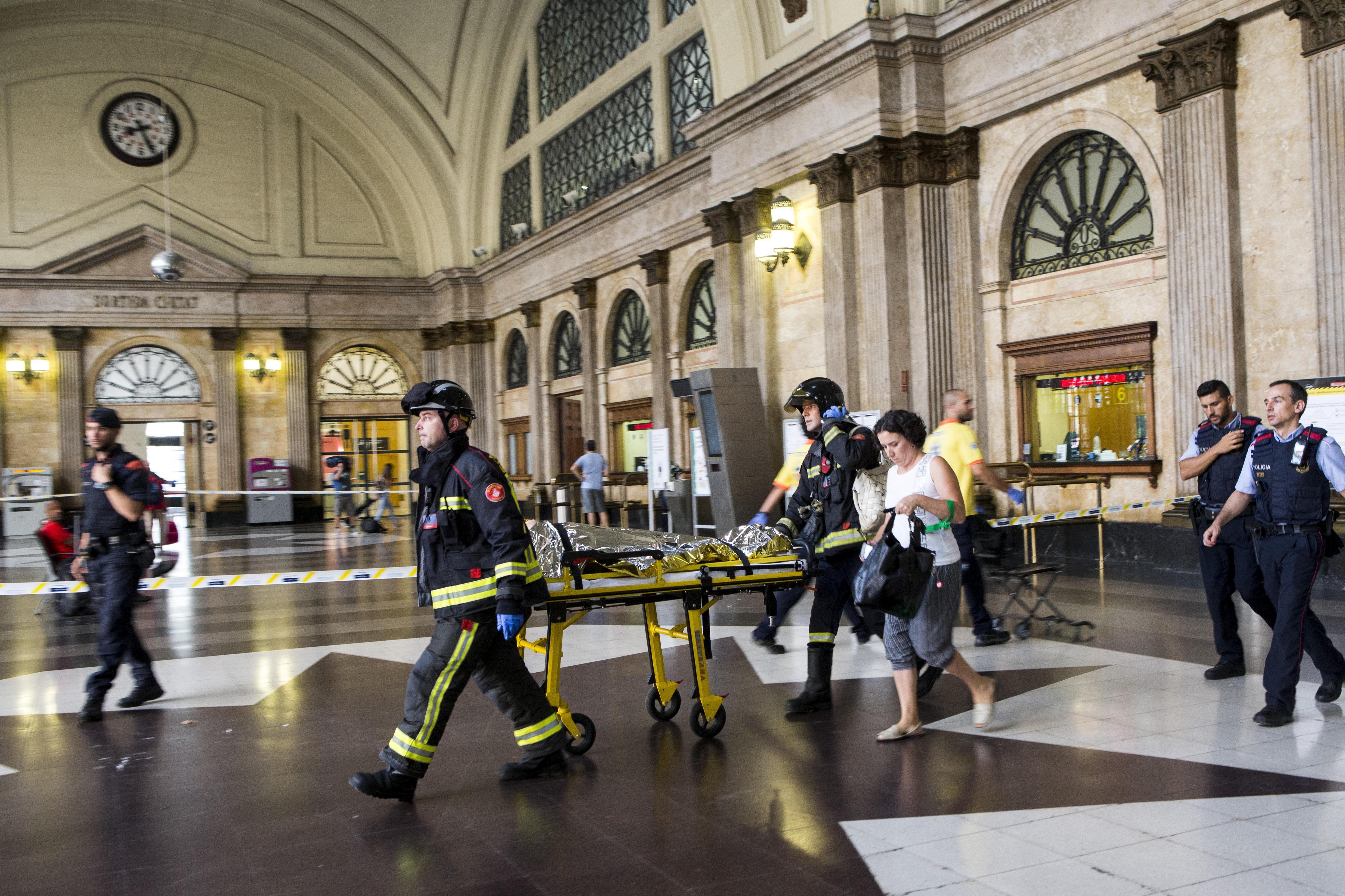 Equips d'emergència atenen els passatgers que han resultat ferits en xocar un tren de Renfe contra el topall final d'una via en l'Estació de França de Barcelona. /QUIQUE GARCÍA