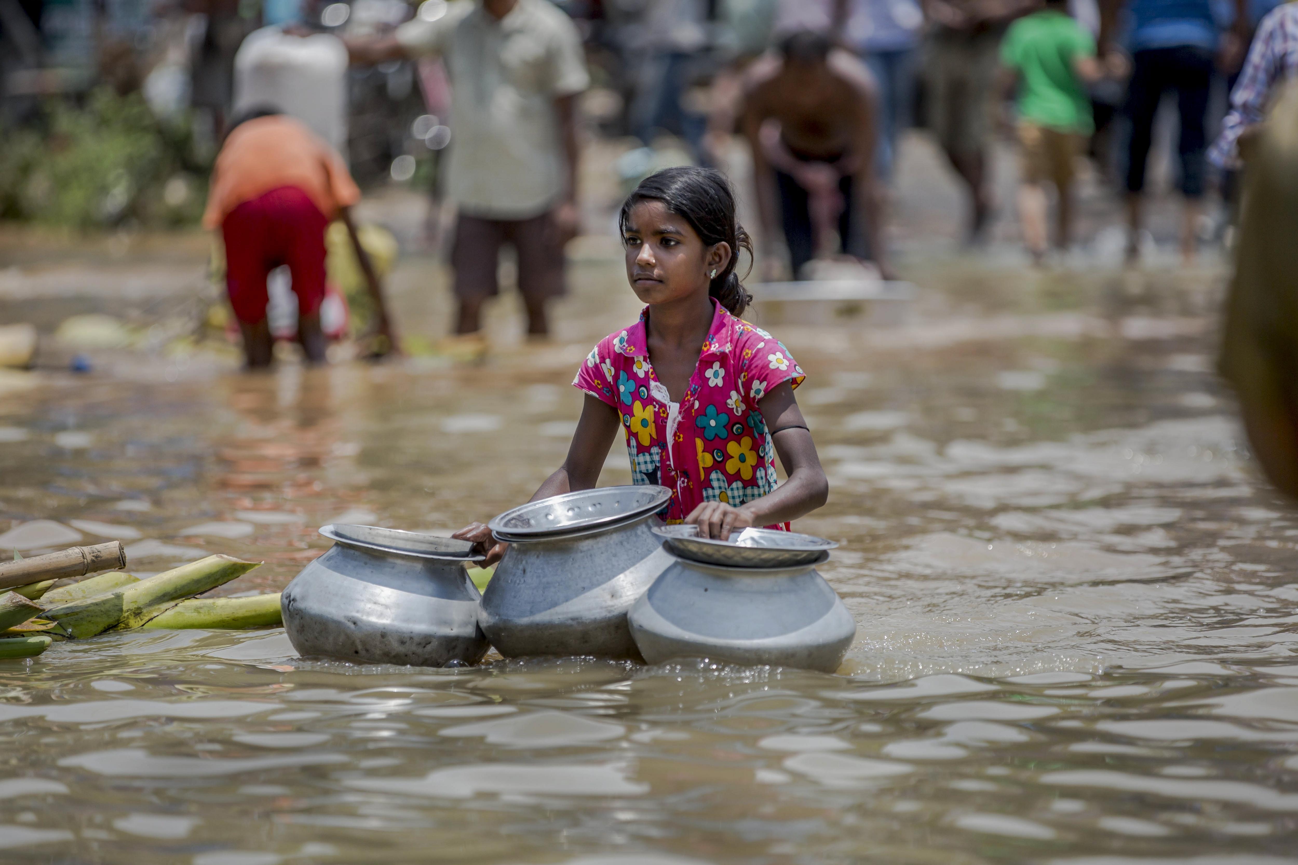 Una nina porta tres càntirs per recollir aigua d'una font enmig d'un carrer inundat d'Amta, a l'Índia. /PIYAL ADHIKARY