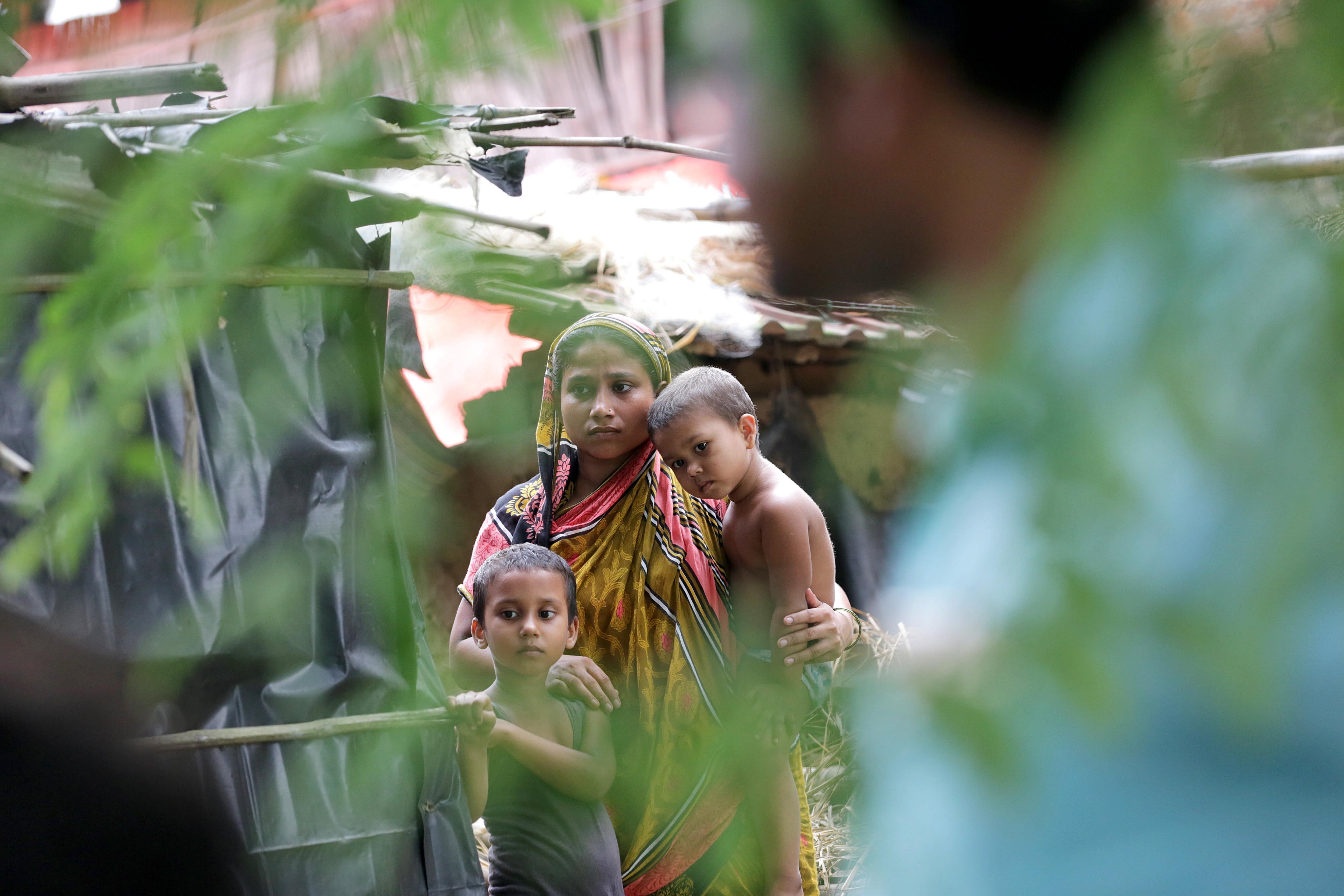 Una família víctima de les inundacions espera l'ajuda alimentària al poble de Pratapur, a l'Índia. /PIYAL ADHIKARY