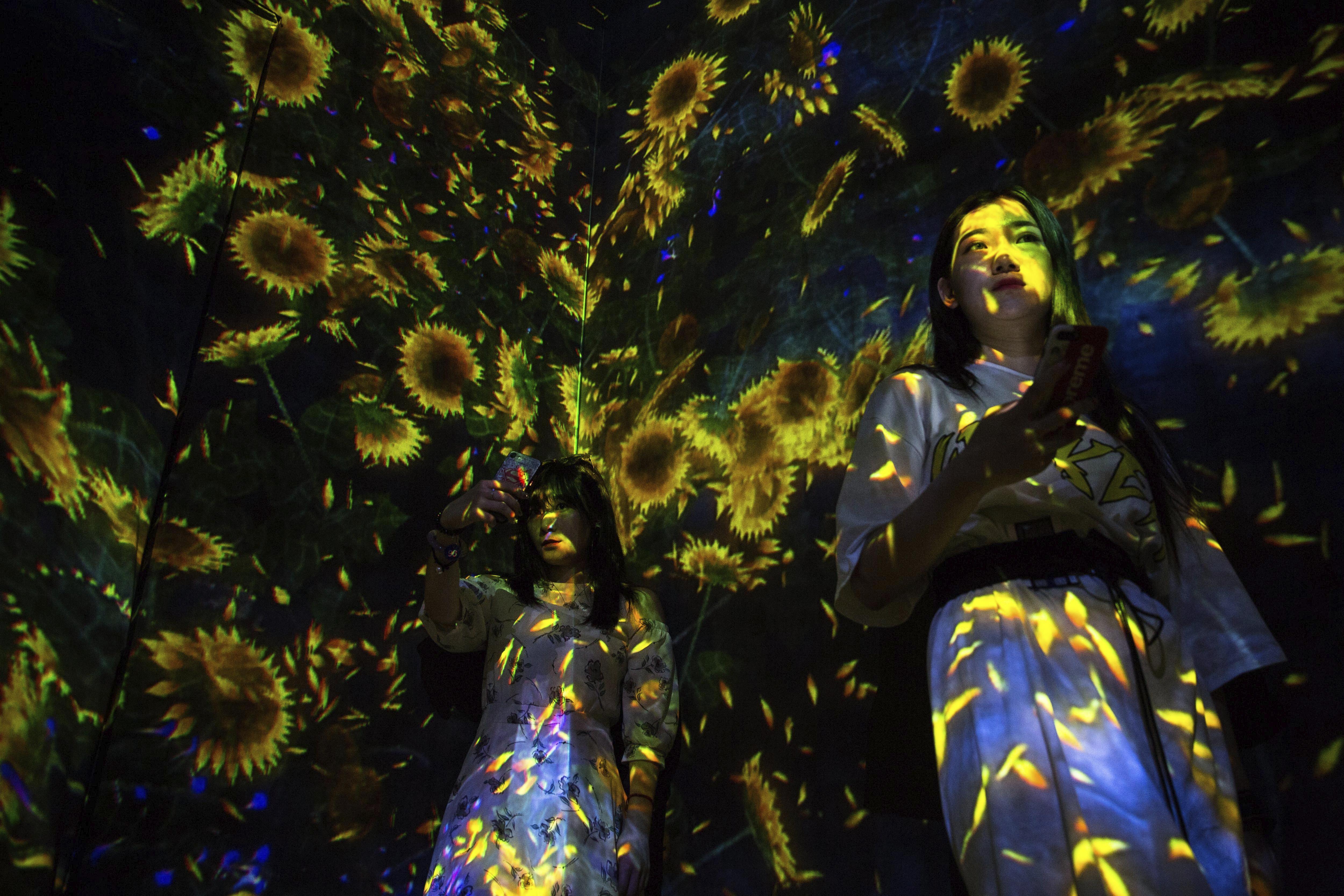 """Dues dones participen en l'exposició """"Living Digital Forest and Future Park"""" a Pequín (Xina). /ROMAN PILIPEY"""