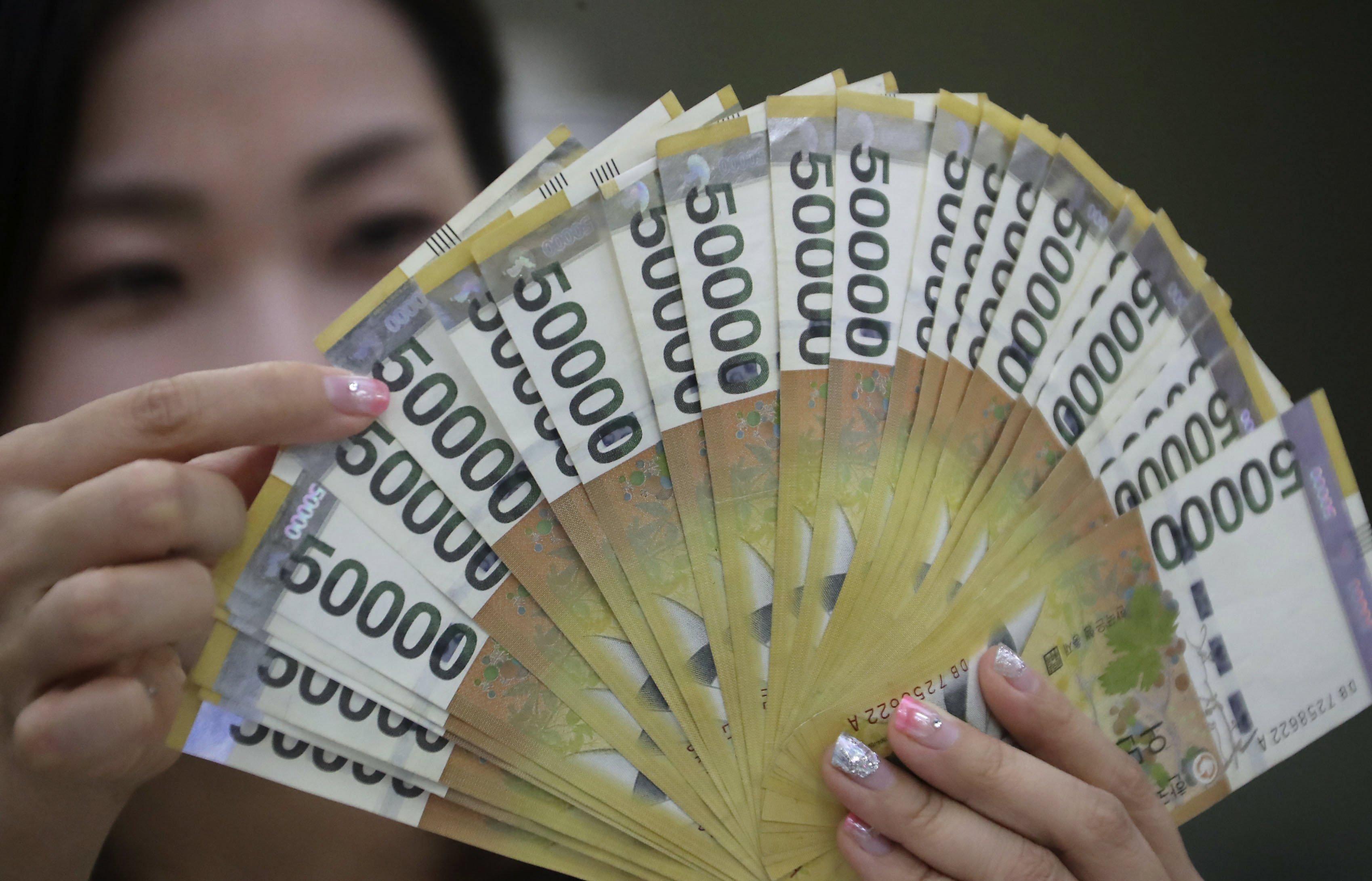 Una treballadora d'un banc mostra diversos bitllets de 50.000 wones (equivalents a 44, 32 dòlars), la moneda local de Corea del Sud, a Seül (Corea del Sud).  /YONHAP