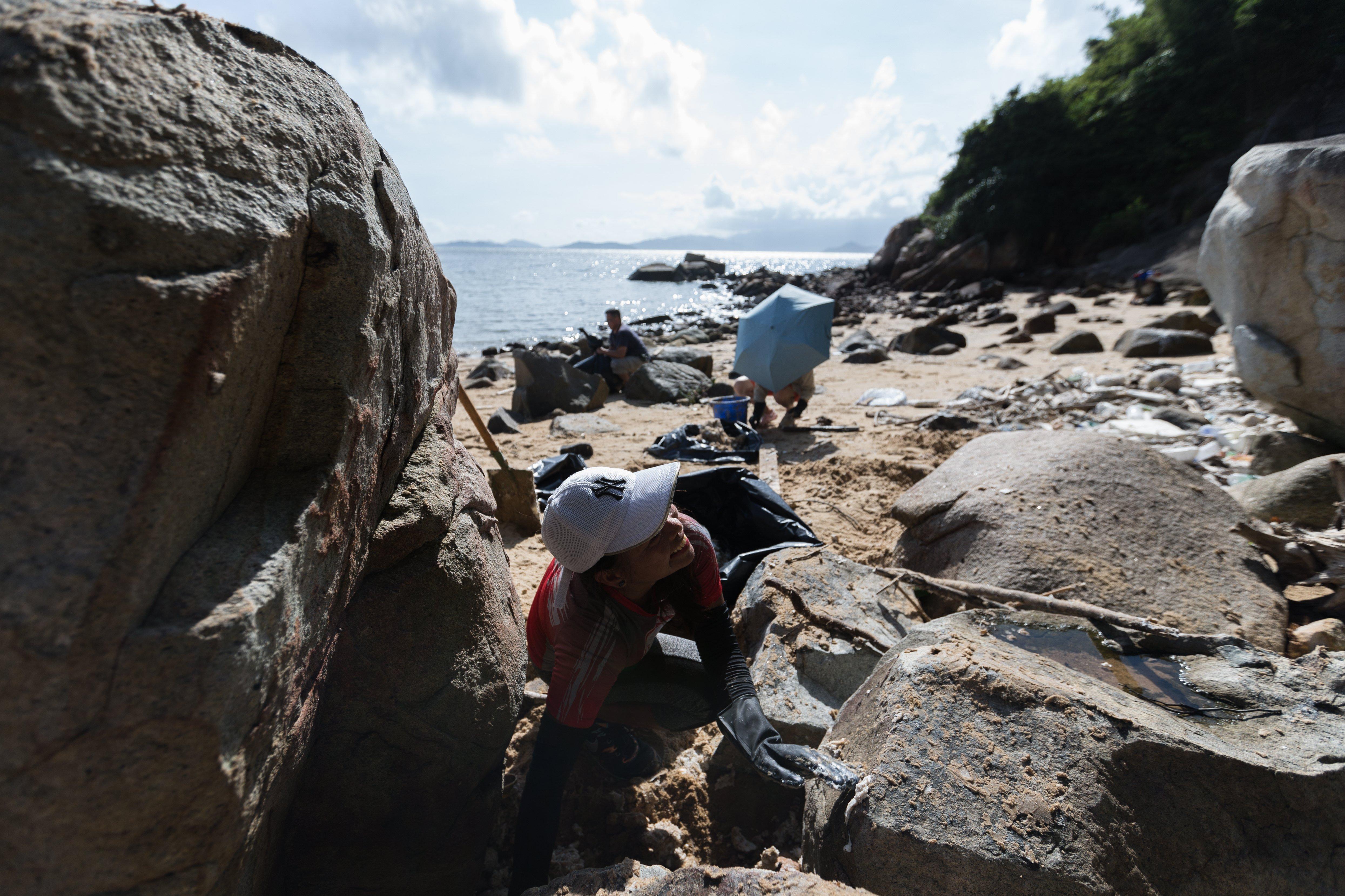 Una voluntària participa en les tasques de neteja d'un abocament d'oli de palma a l'illa de Lamma a Hong Kong (Xina). /VERNON YUEN