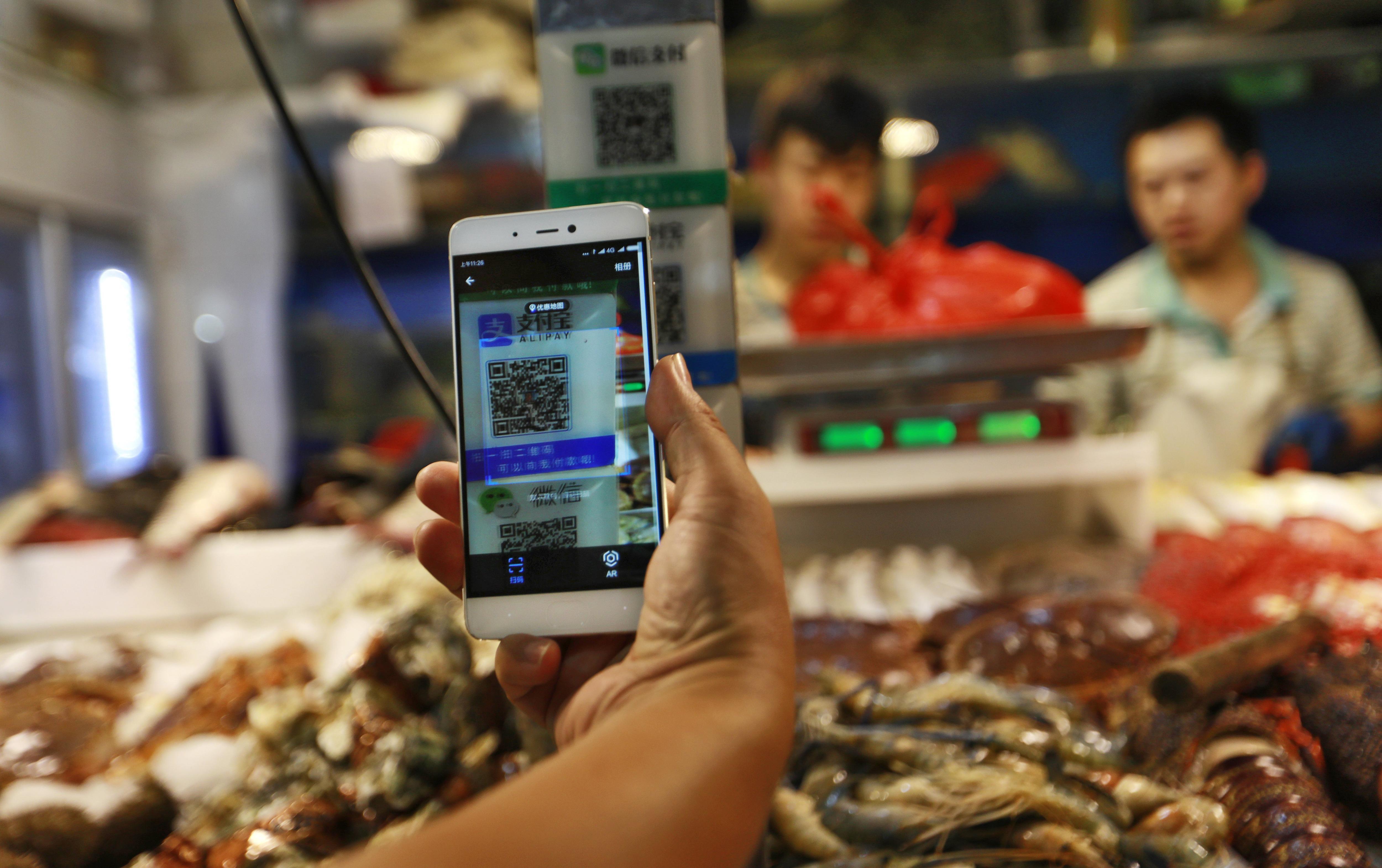 Un client escaneja un codi QR de Alipay per realitzar un pagament a través d'un telèfon mòbil en un mercat a Pequín. L'IPC de Xina ha pujat un 1,4%. /HOW HWEE YOUNG