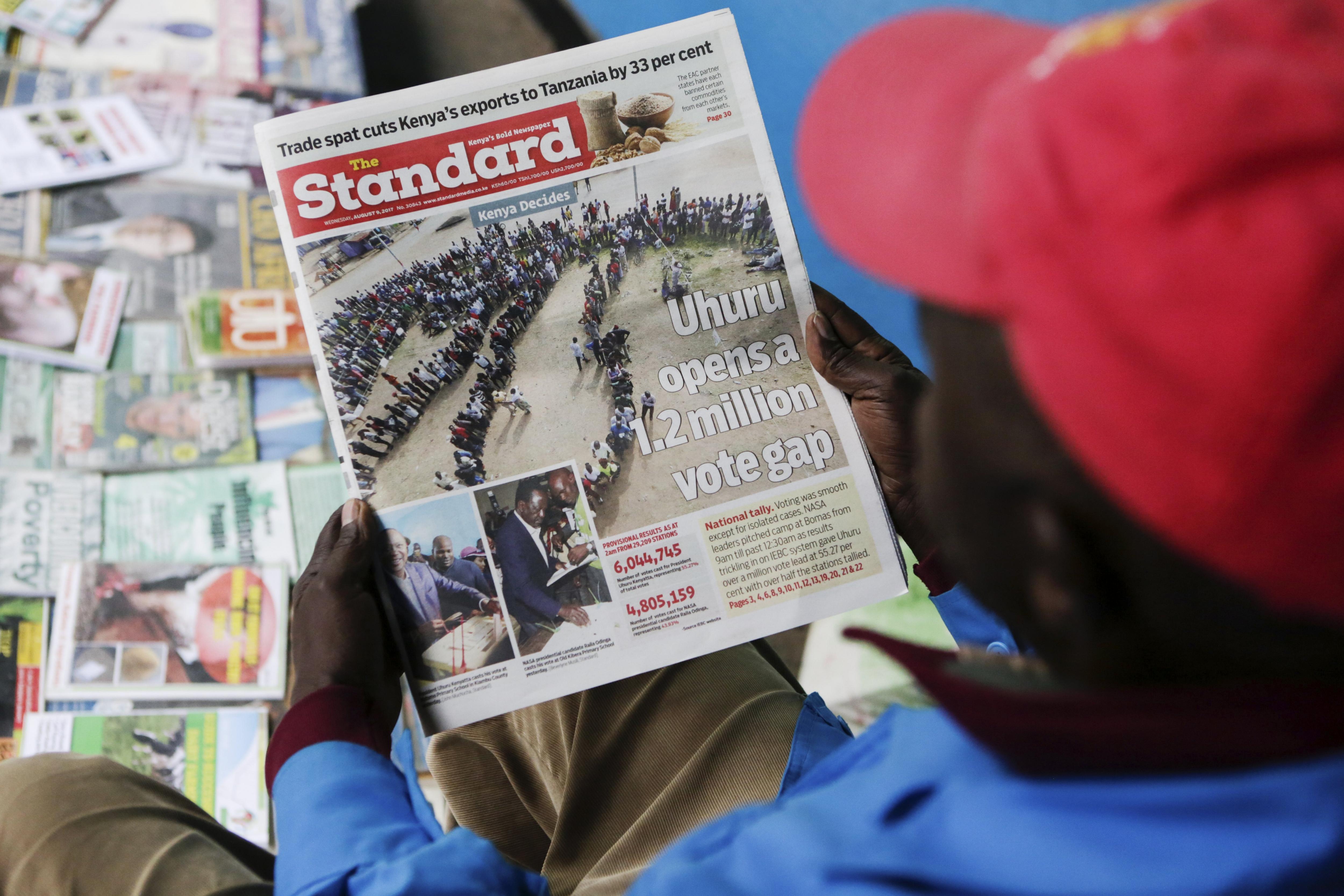 Un venedor de diaris llegeix la portada d'un diari local a Nairobi. El president de Kenya lidera els resultats provisionals amb un 54,69%. /DANIEL IRUNGU