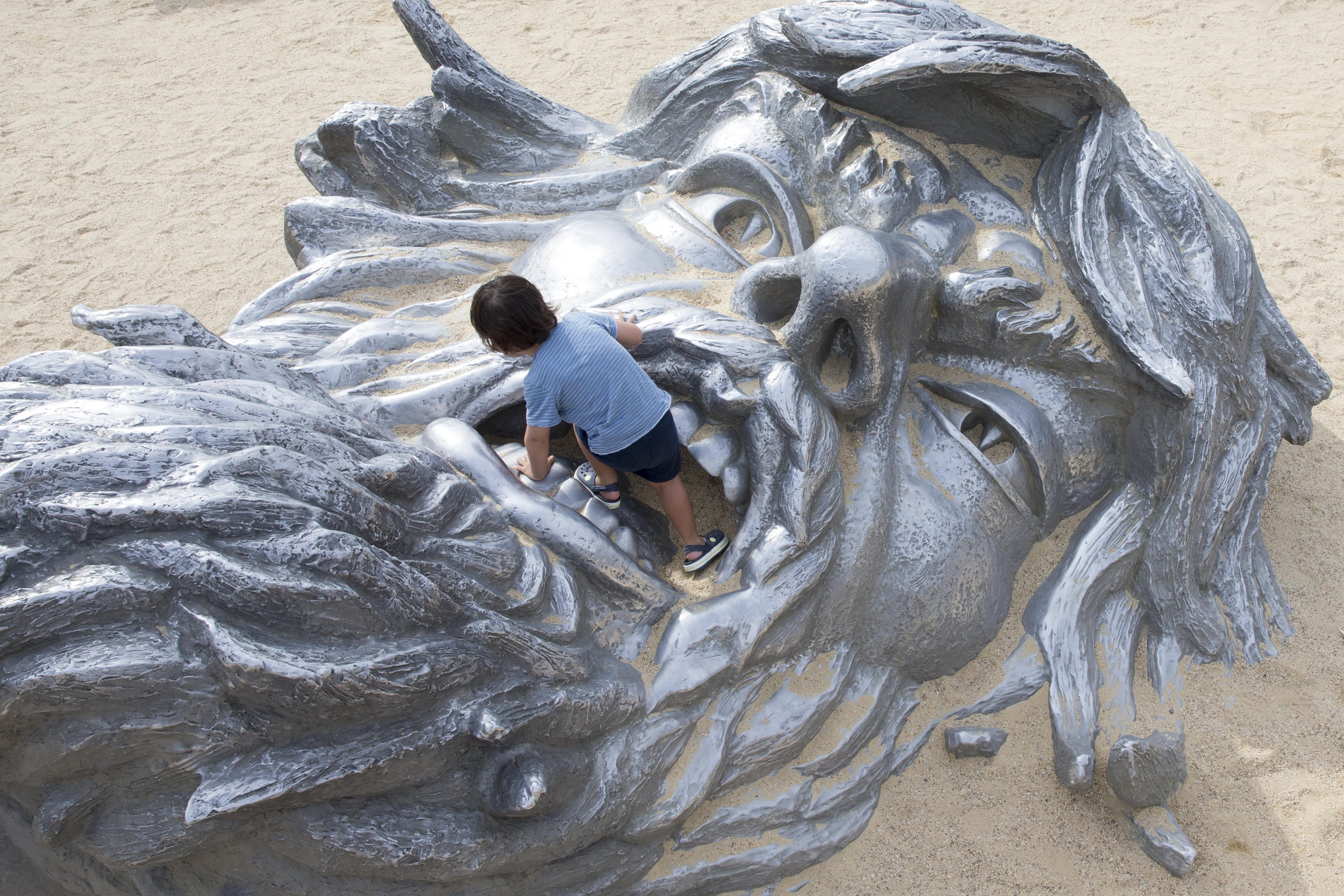 Un nin juga al lloc on hi ha l'estàtua titulada 'Despertar' a National Harbor, Maryland, EUA. /MICHAEL REYNOLDS