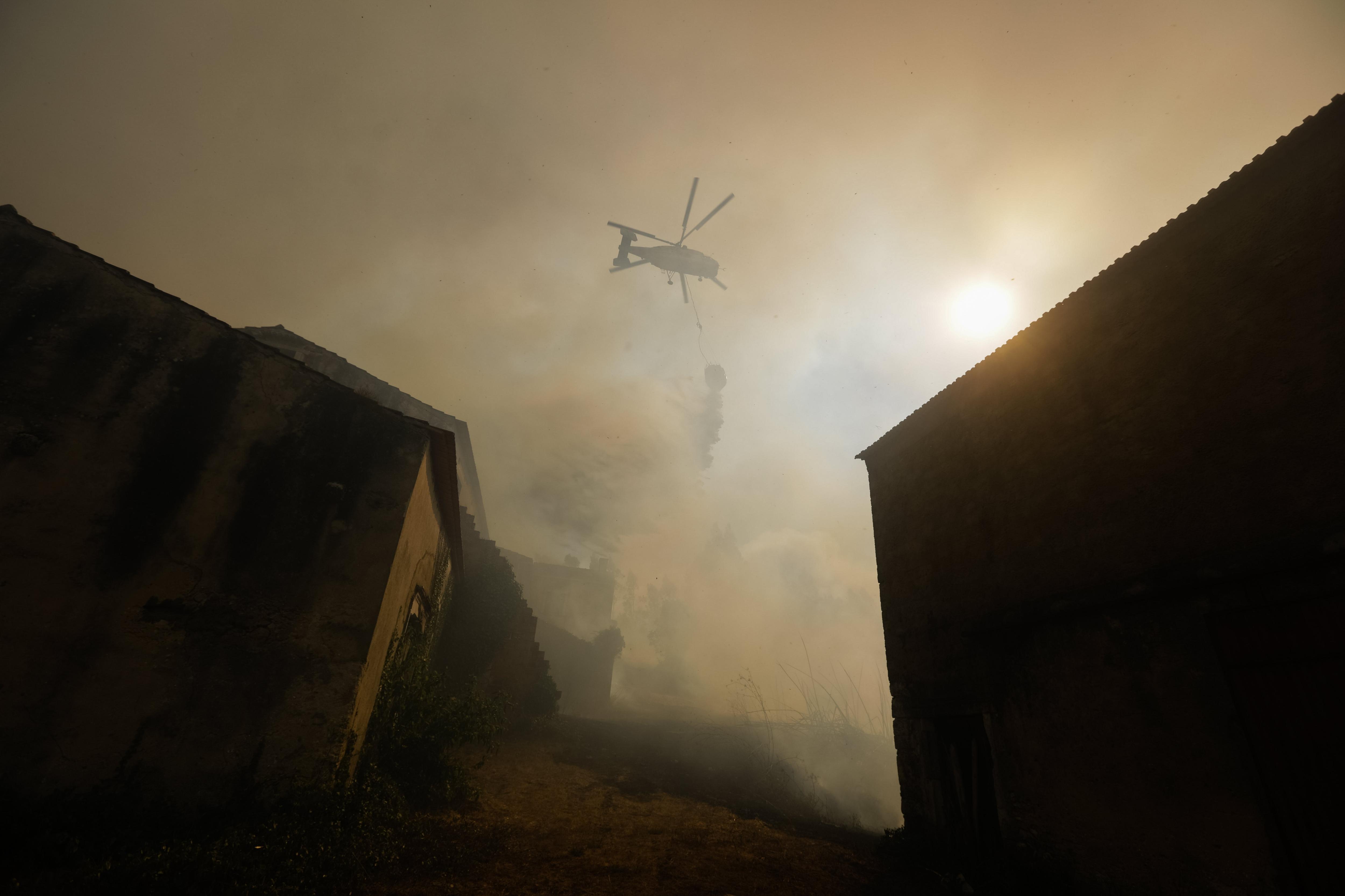Un helicòpter llança aigua sobre un incendi forestal a Vila Pisao, Mealhada (Portugal). /PAULO NOVAIS