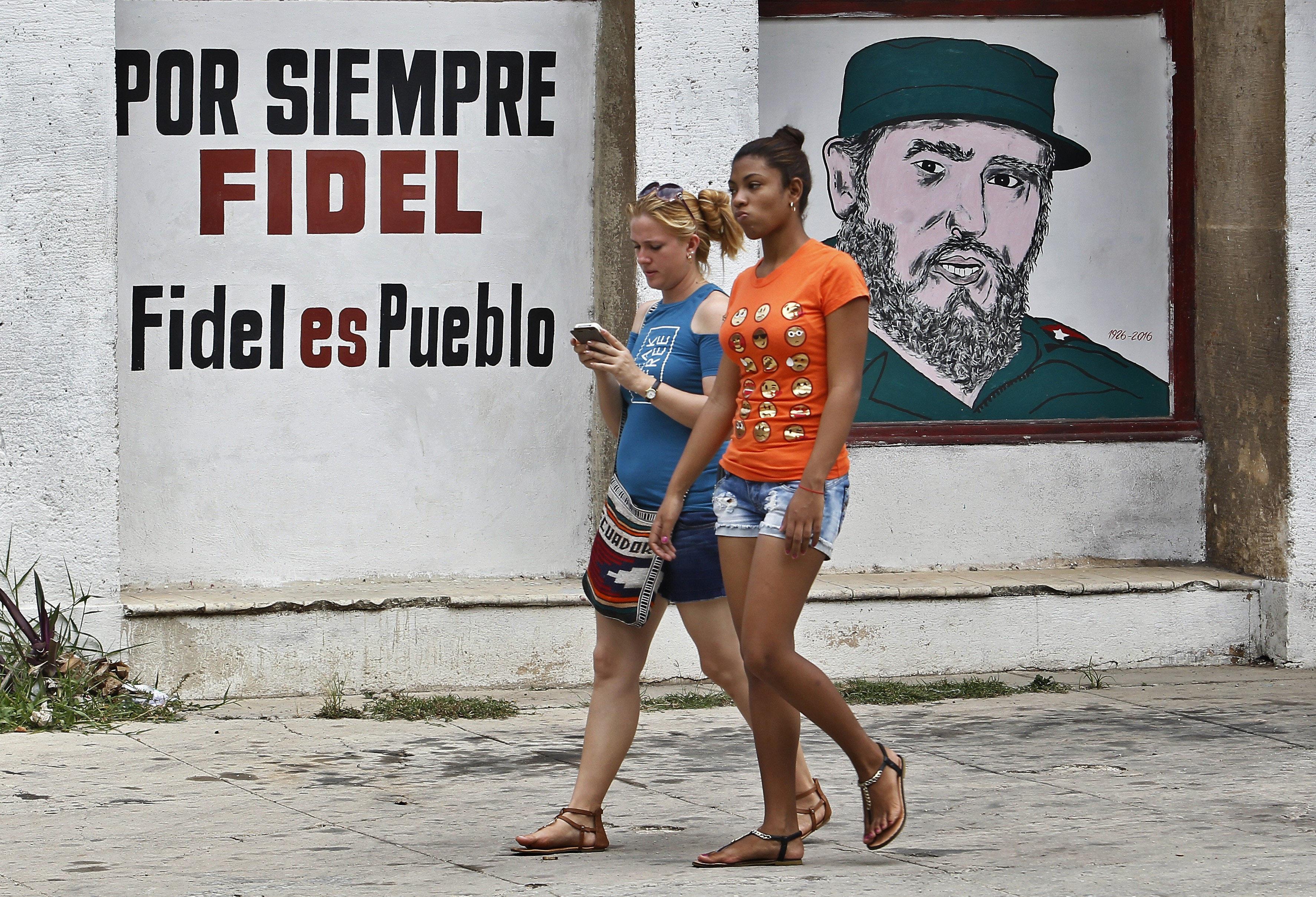 Dues joves passen davant d'un grafit amb la imatge del cap de la revolució cubana, Fidel Castro, el dia del seu 91 aniversari a l'Havana (Cuba). /E. MASTRASCUSA