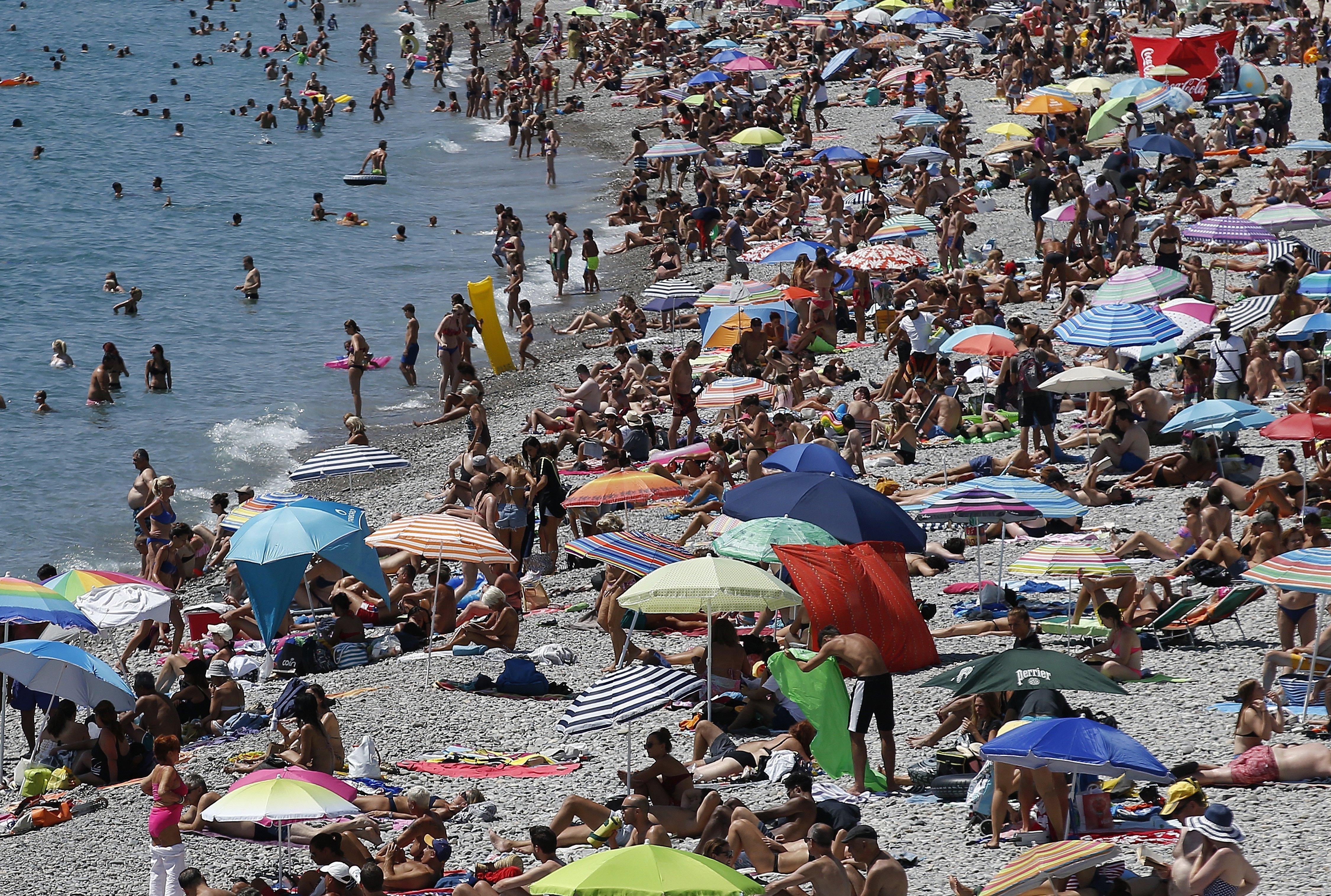 """Diverses persones gaudeixen de la platja en la """"Promenade des Anglais"""" a Niça, sud de França, avui, 15 d'agost de 2017. Les temperatures han aconseguit avui els 39 graus centígrads. /Sebastien Nogier"""