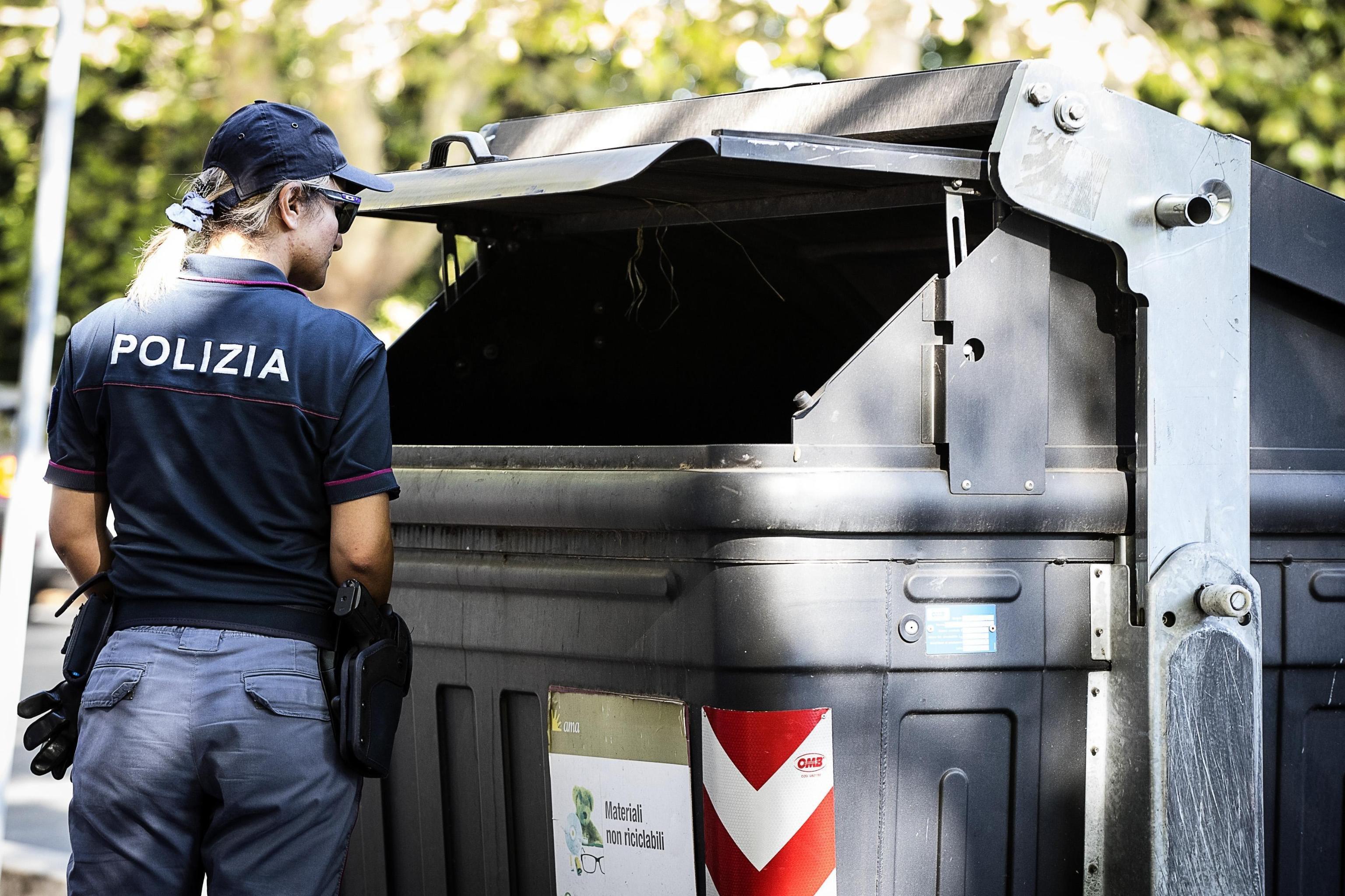 Diversos membres de la policia italiana acordonen un contenidor d'escombraries al barri residencial de Parioli a Roma, en el qual s'han trobat dues cames de dona amputades (Itàlia). /ANGELO CARCONI