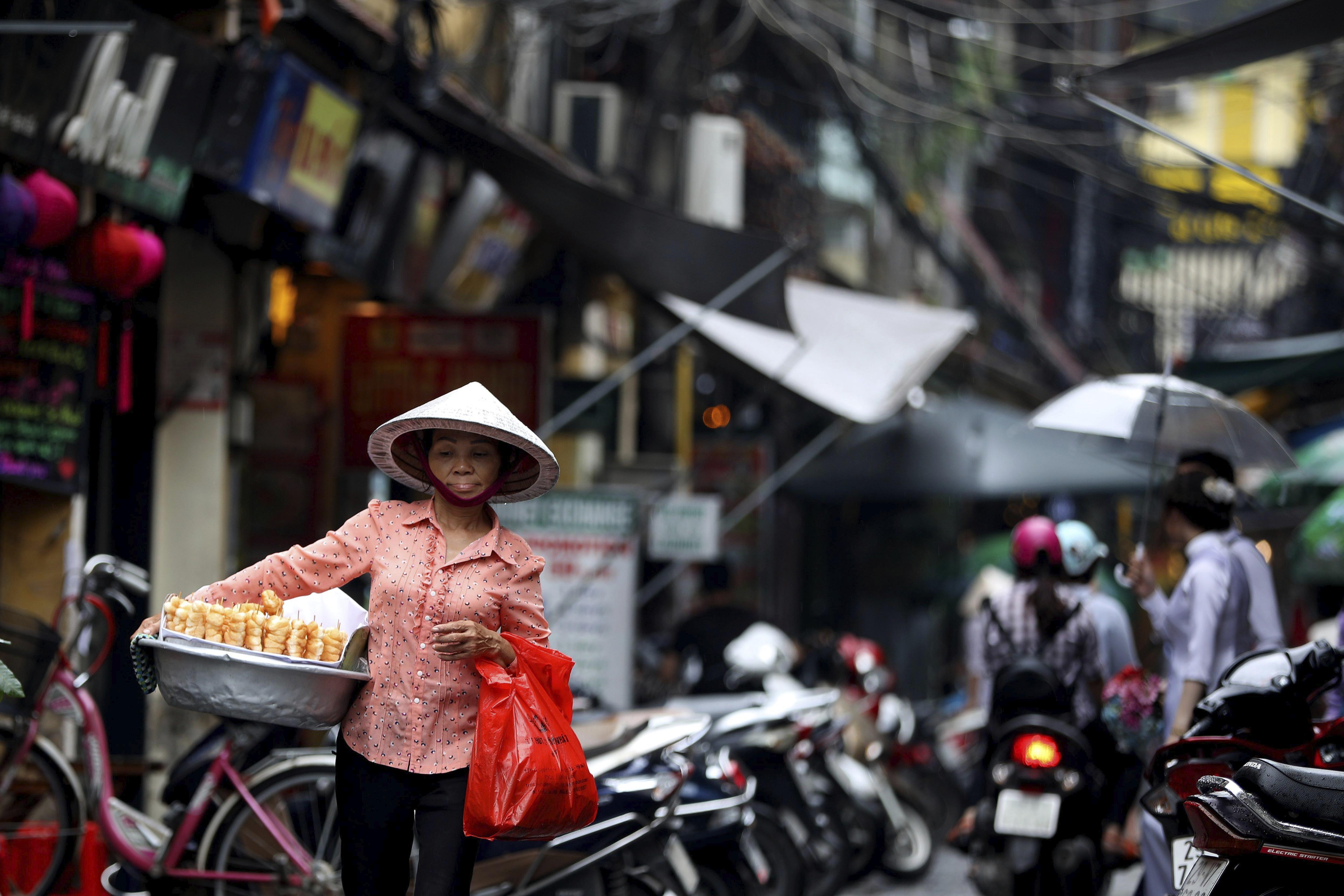 Una venedora recorre un carrer a Hanoi (Vietnam). Es preveu que el PIB vietnamita creixi un 6,5% aquest any. /LUONG THAI LINH