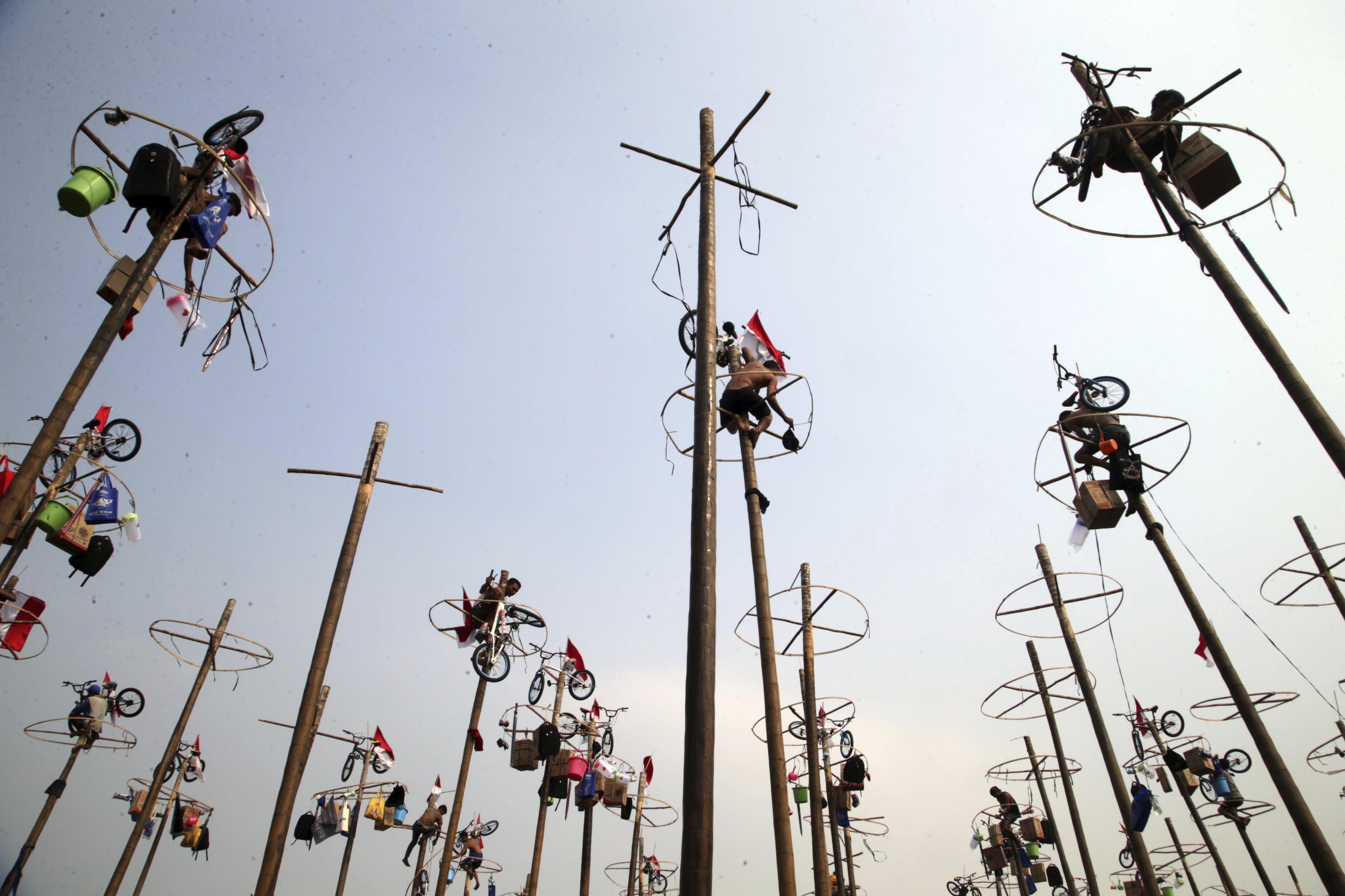 Diversos ciutadans competeixen per aconseguir els regals penjats als pals durant les celebracions pel 72º Dia de la Independència a Jakarta (Indonèsia). /BAGUS INDAHONO