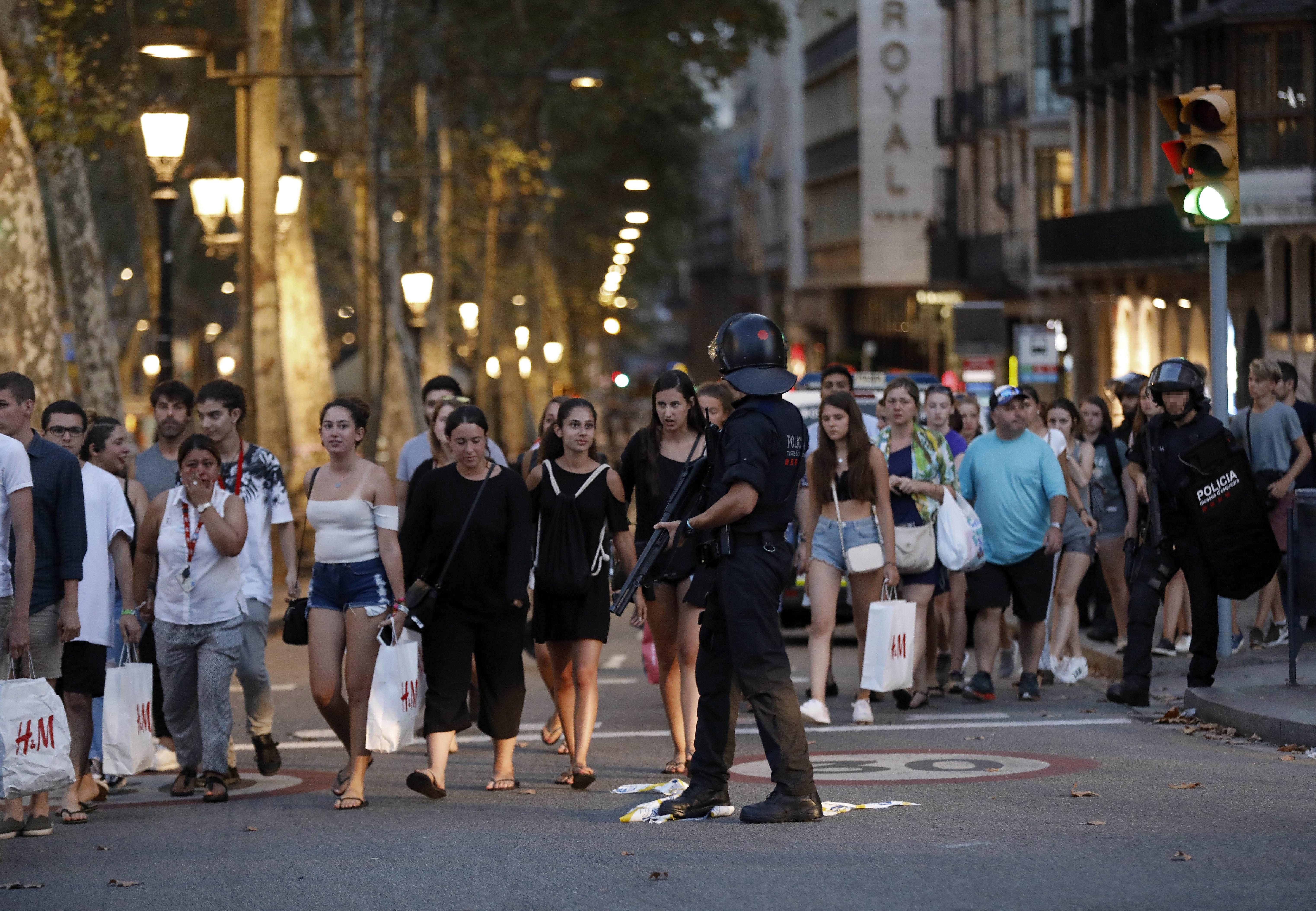 Un grup de gent es desplaça entre el desplegament policial en el lloc de l'atemptat ocorregut a les Rambles de Barcelona. /ANDREU DALMAU
