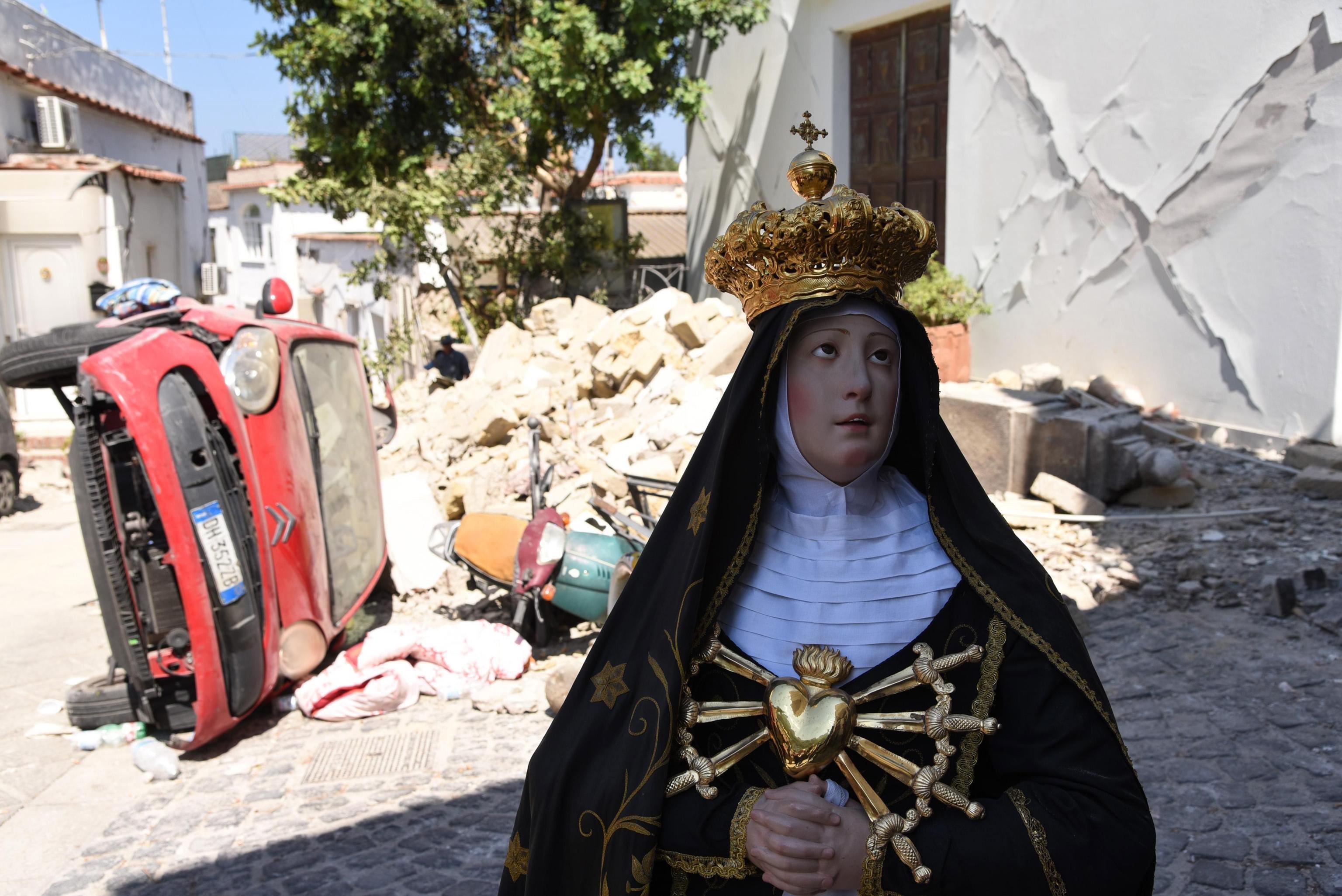 Vista d'una imatge d'una Mare de Déu catòlica rescatada de l'església del Purgatori al costat d'alguns danys del terratrèmol a Ischia, Itàlia./Corrado Amitrano