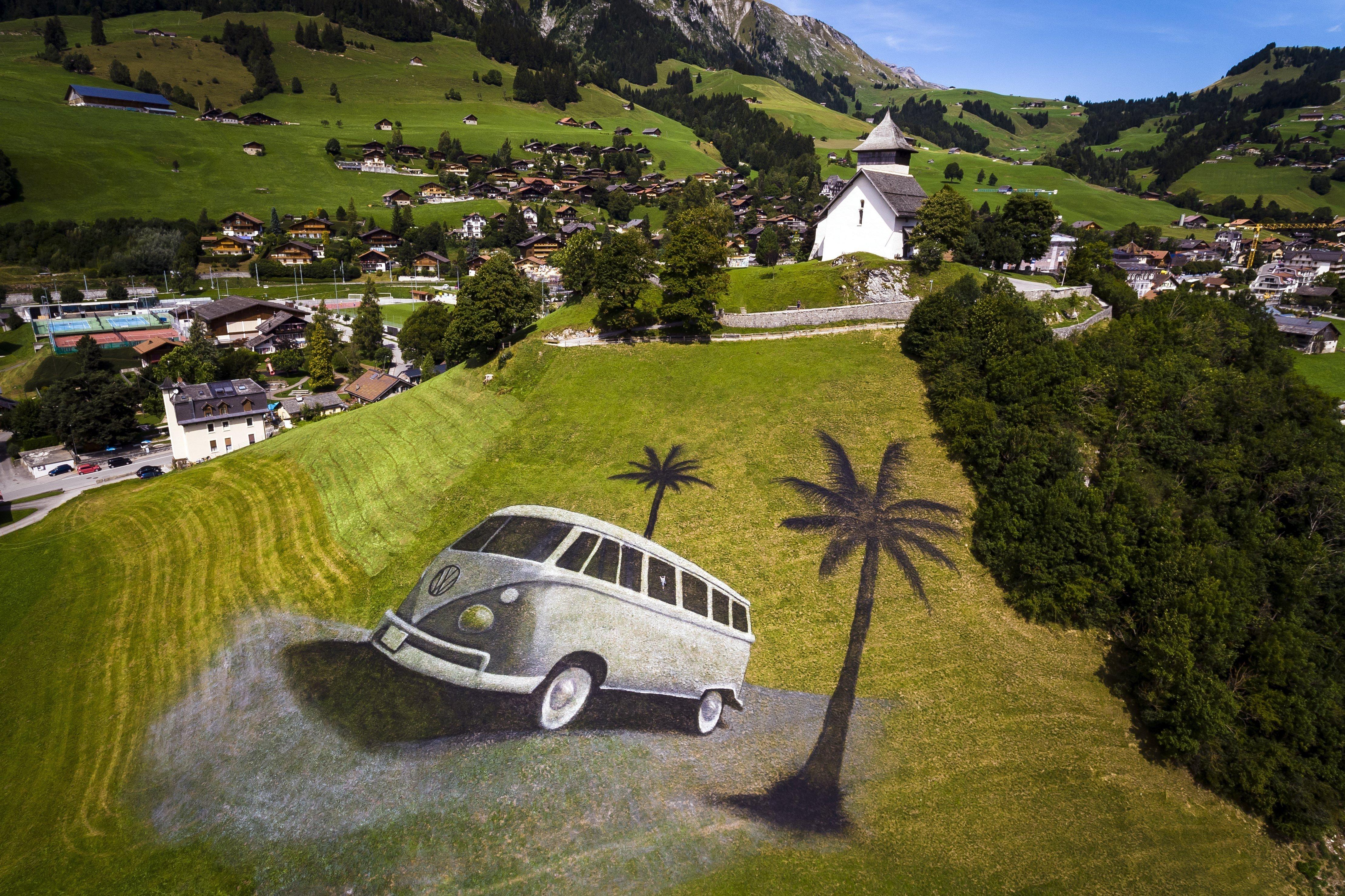 Vista aèria d'una pintura de l'artista francès Saype d'una furgoneta Volkswagen a Chateaux d'Oex, a Suïssa. L'obra cobreix aproximadament 4.200 metres quadrats i es va realitzar amb 400 litres de pintura biodegradable feta amb pigments naturals, i forma part de la propera 20a edició del festival internacional VW./Valentin Flauraud