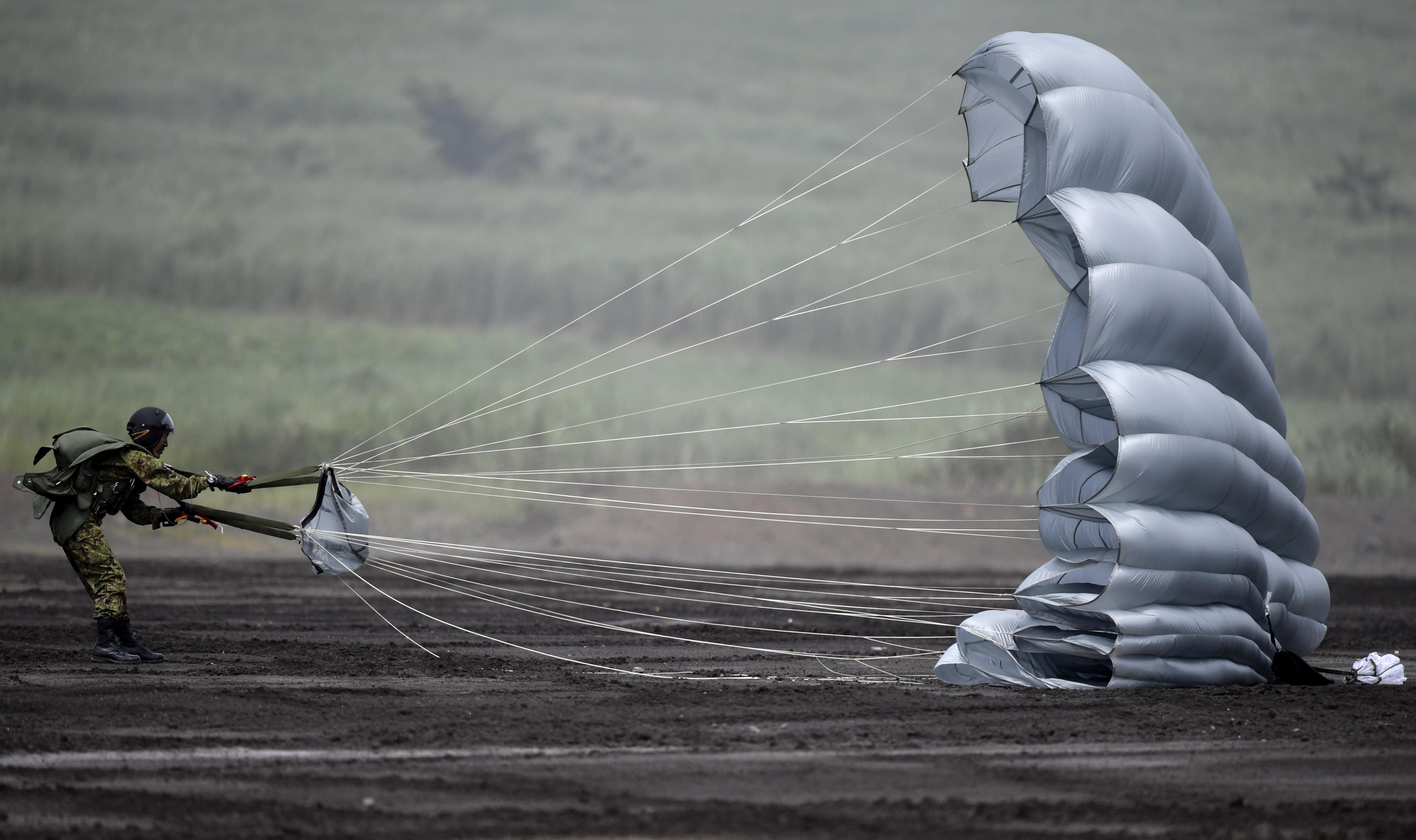 Un paracaigudista de les Forces de Terra japoneses recull el seu paracaigudes després de prendre terra durant unes maniobres amb foc real en el camp d'entrenament d'Higashi Fuji, al Japó. /FRANCK ROBICHON