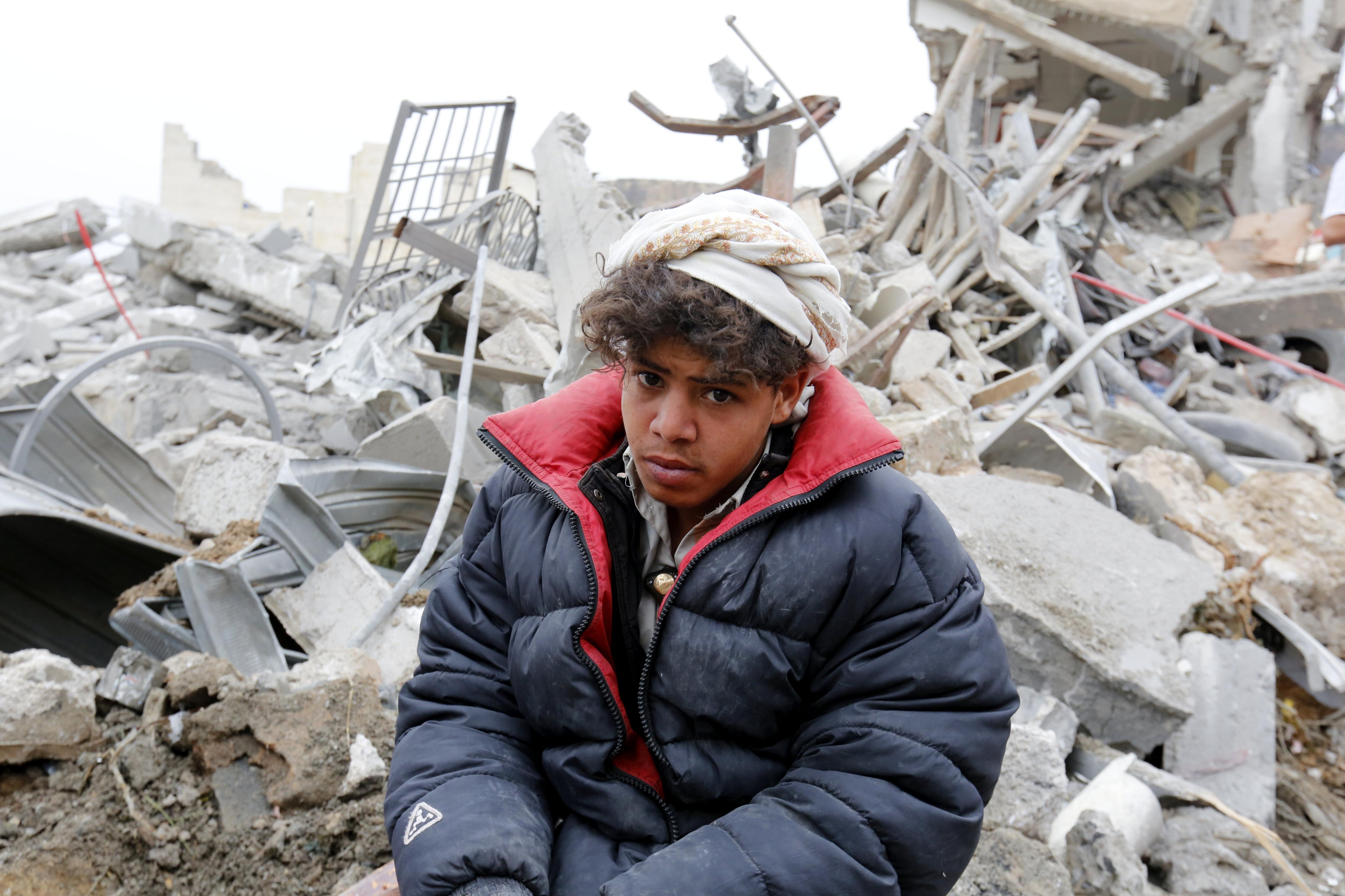 Un iemenita assegut entre les restes d'un edifici després d'un bombardeig de la coalició liderada per Aràbia Saudita a Sanà, Iemen, que ha causat la mort d'almenys dotze persones i deu ferits, segons els equips de rescat./Yahya Arhab