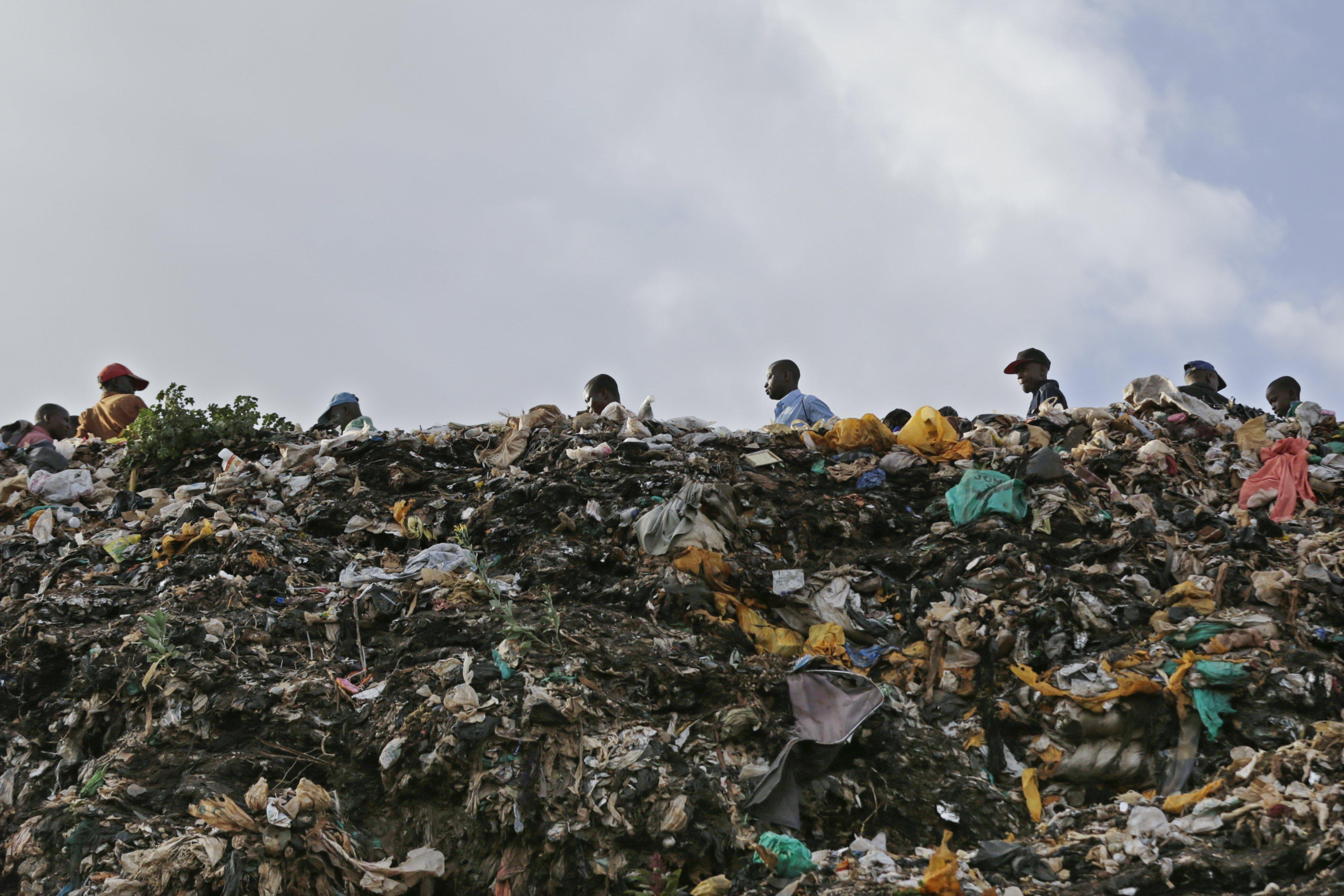 Diverses persones caminen al costat d'un munt d'escombraries al barri de Mathare a Nairobi. Avui entra en vigor la prohibició de les bosses de plàstic (Kenya). /DAI KUROKAWA
