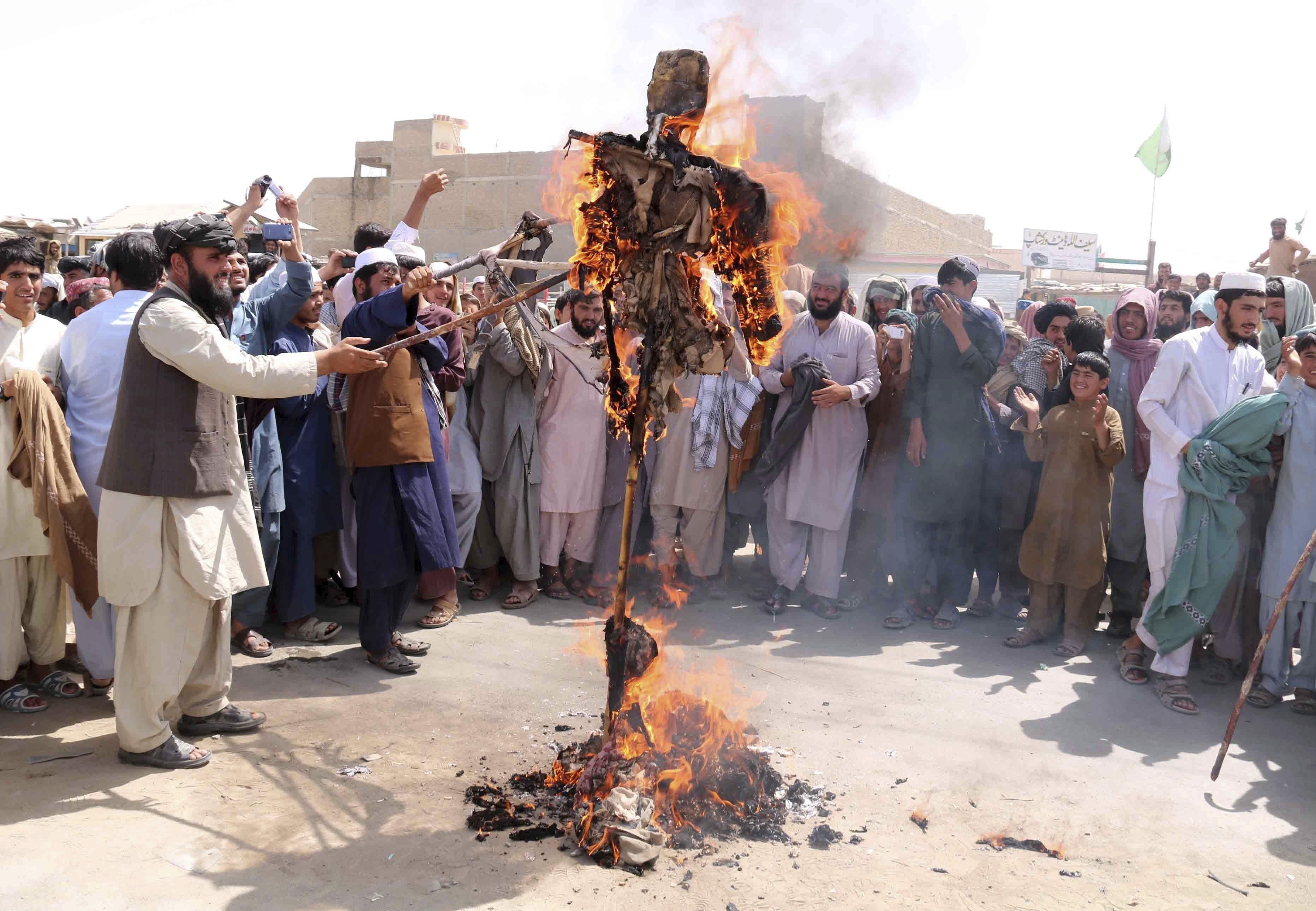 Diverses persones cremen una efígie amb la forma del president nord-americà, Donald Trump, prop de la frontera afganesa en Chaman (Pakistan). /AKHTER GULFAM