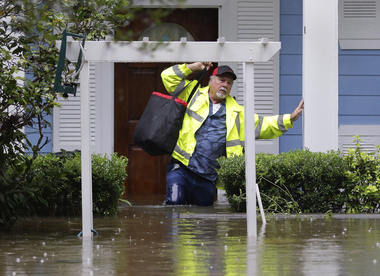 Un home treu una bossa d'aliments de casa seva després de l'huracà Harvey a Texas, als Estats Units. /MICHAEL WYKE