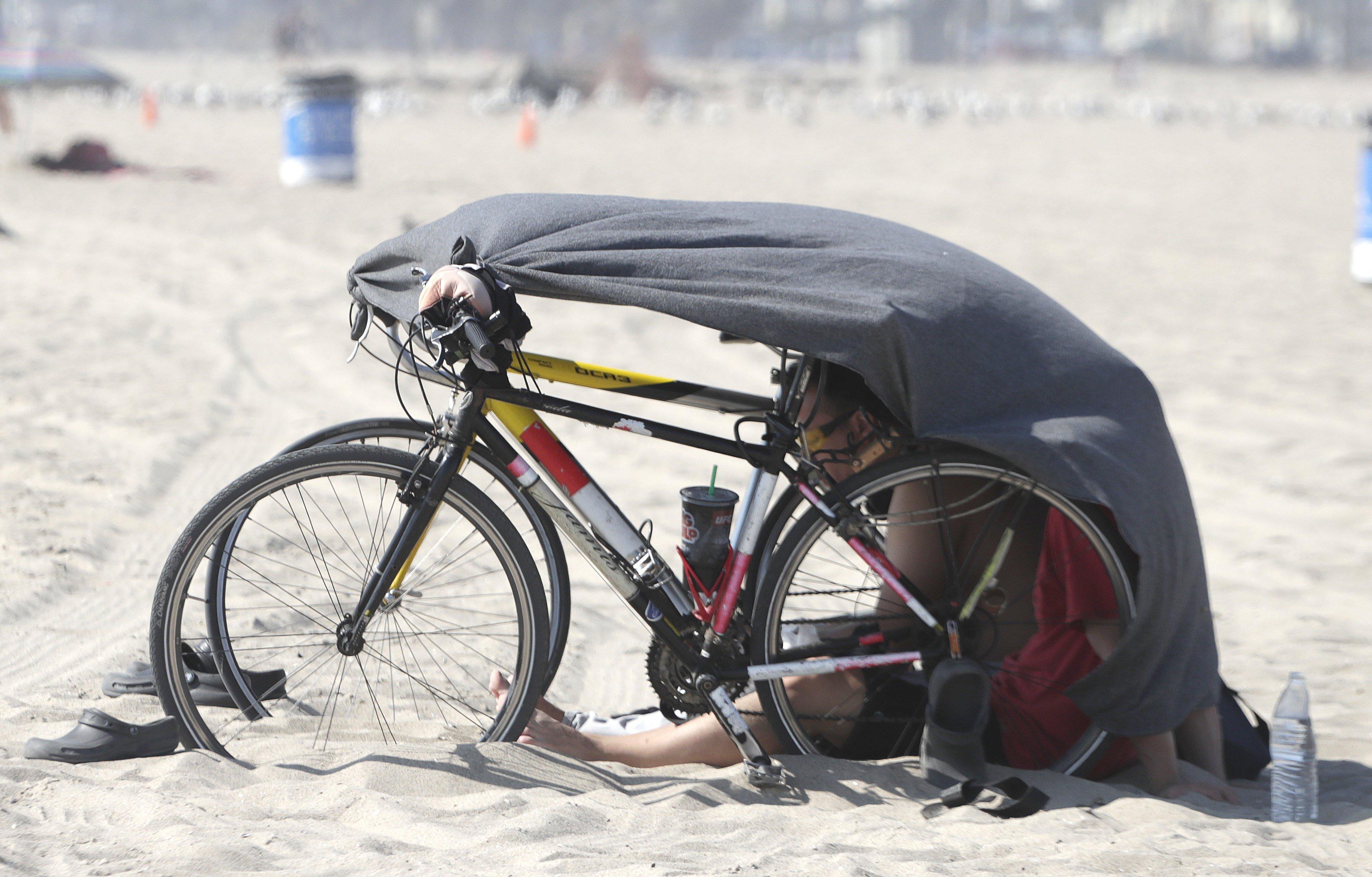 Un banyista es protegeix del sol enmig d'una onada de calor a la platja Venice a Los Angeles (CA, EUA). /MIKE NELSON