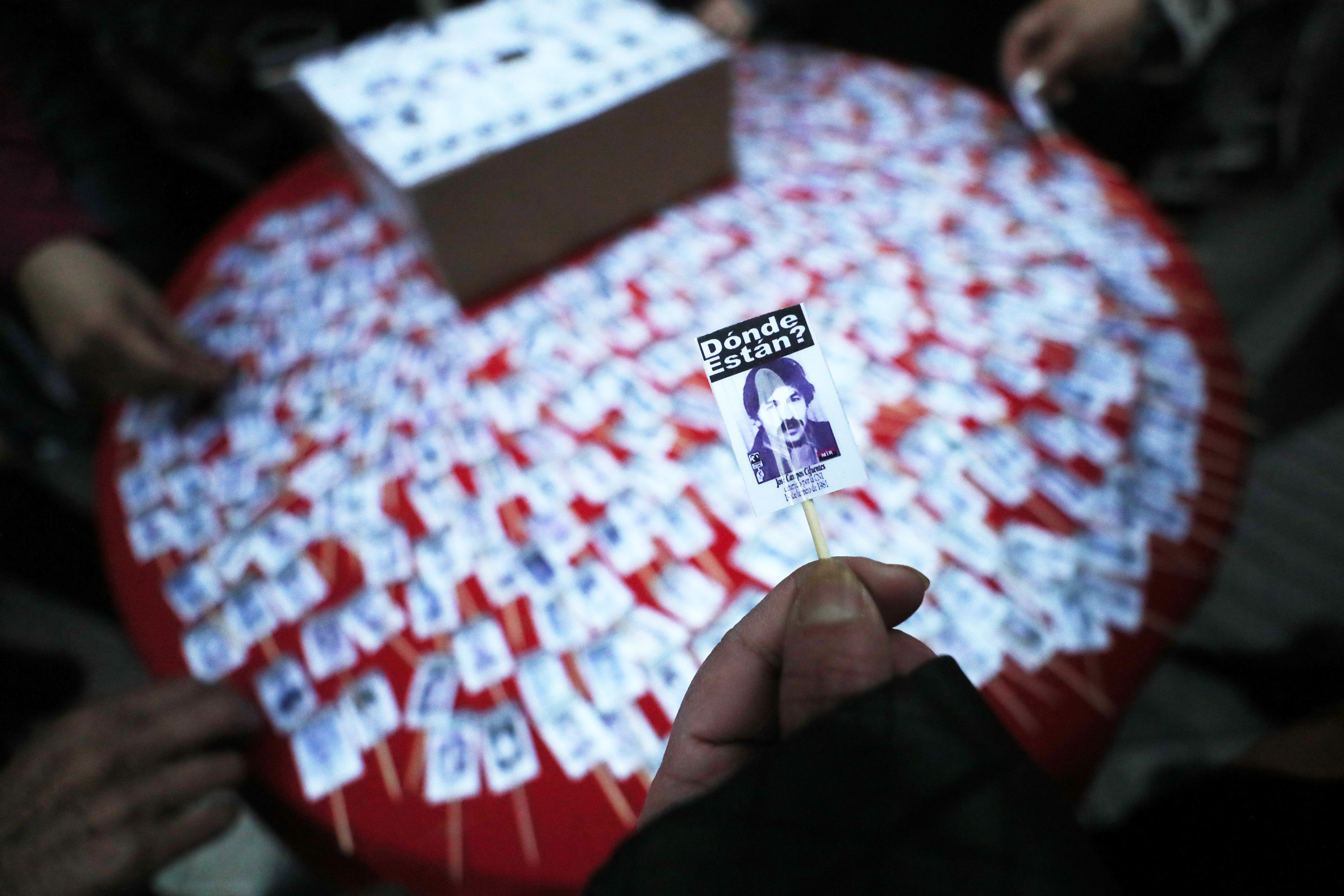 Una persona observa la fotografia d'un detingut desaparegut en un acte de commemoració del Dia Internacional de les Víctimes de Desaparicions Forçades, a Santiago (Xile). /MARIO RUIZ