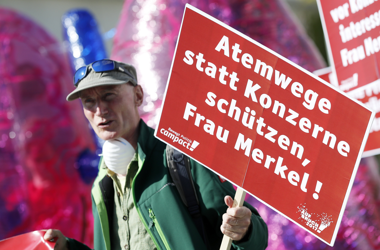 """Un manifestant sosté una pancarta en la qual es llegeix """"Senyora Merkel: protegeix les vies respiratòries en lloc de les grans corporacions"""" mentre participa en una protesta davant la Cancelleria de Berlín (Alemanya). /FELIPE TRUEBA"""