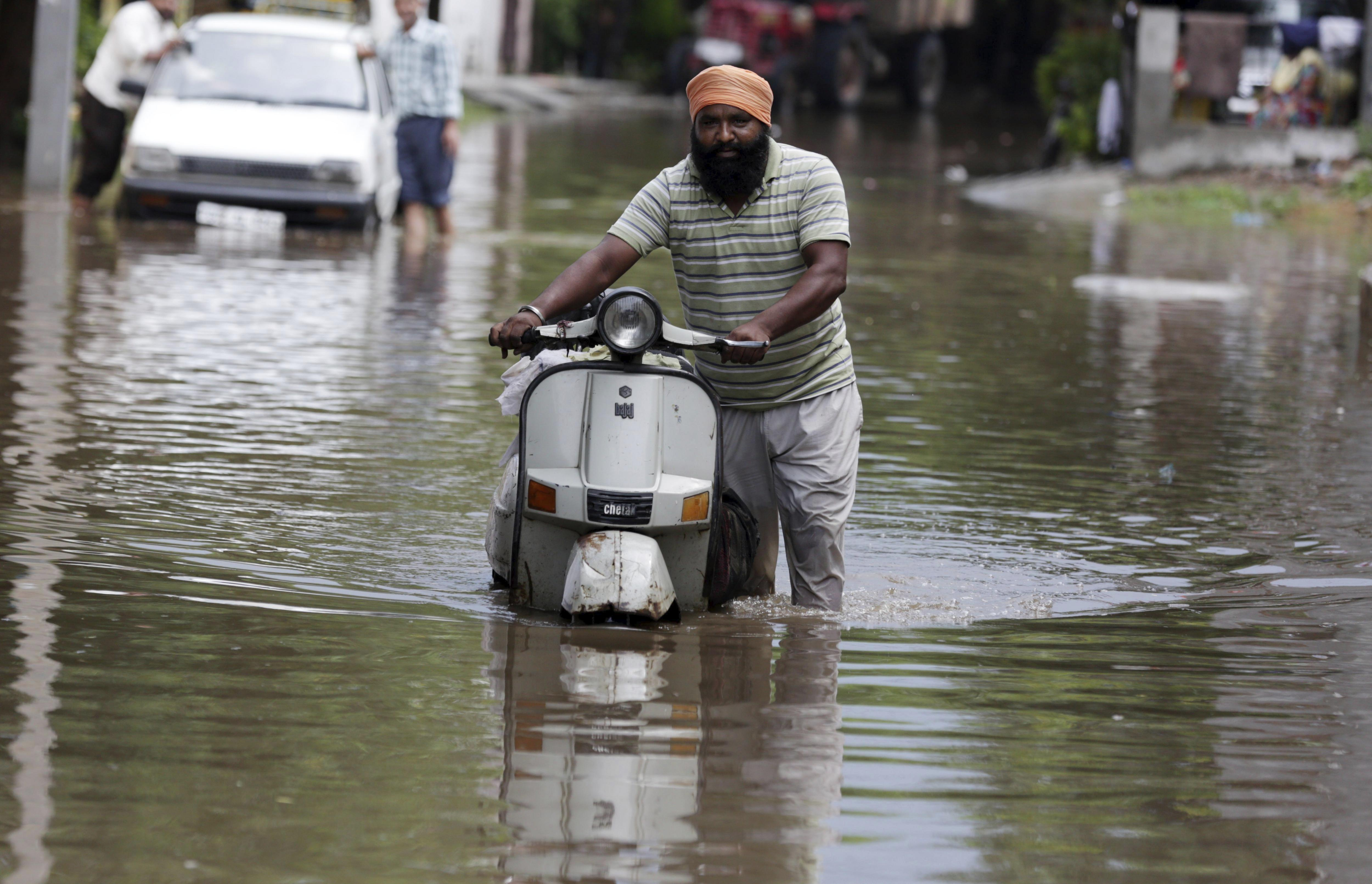 Un home empeny la seva motocicleta per un carrer inundat d'aigua a Amritsar (Índia). /RAMINDER PAL SINGH