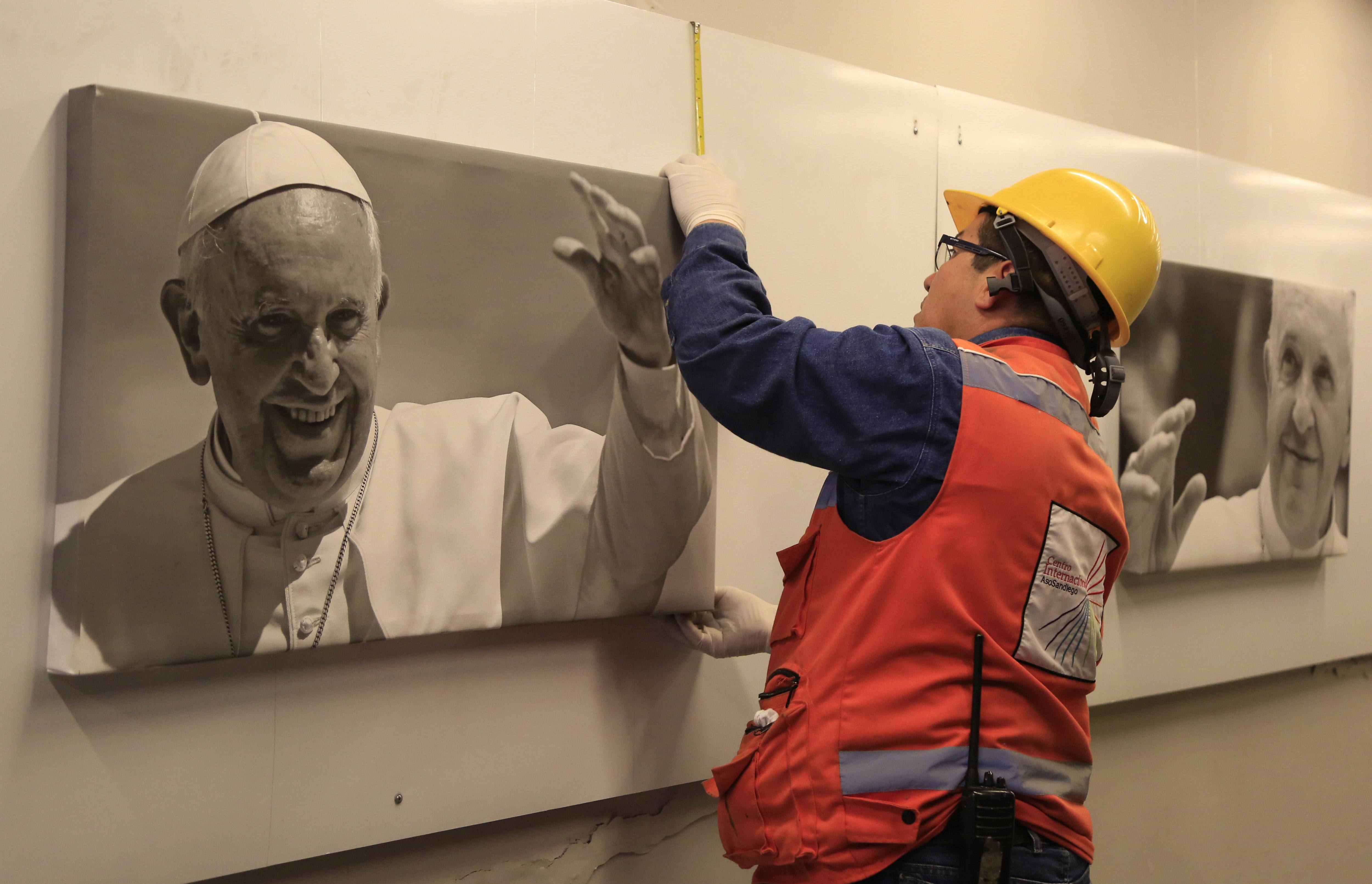 Un home penja unes fotografies del papa Francesc en un dels passatges subterranis del centre de Bogotà (Colòmbia). /RICARDO MALDONADO ROZO