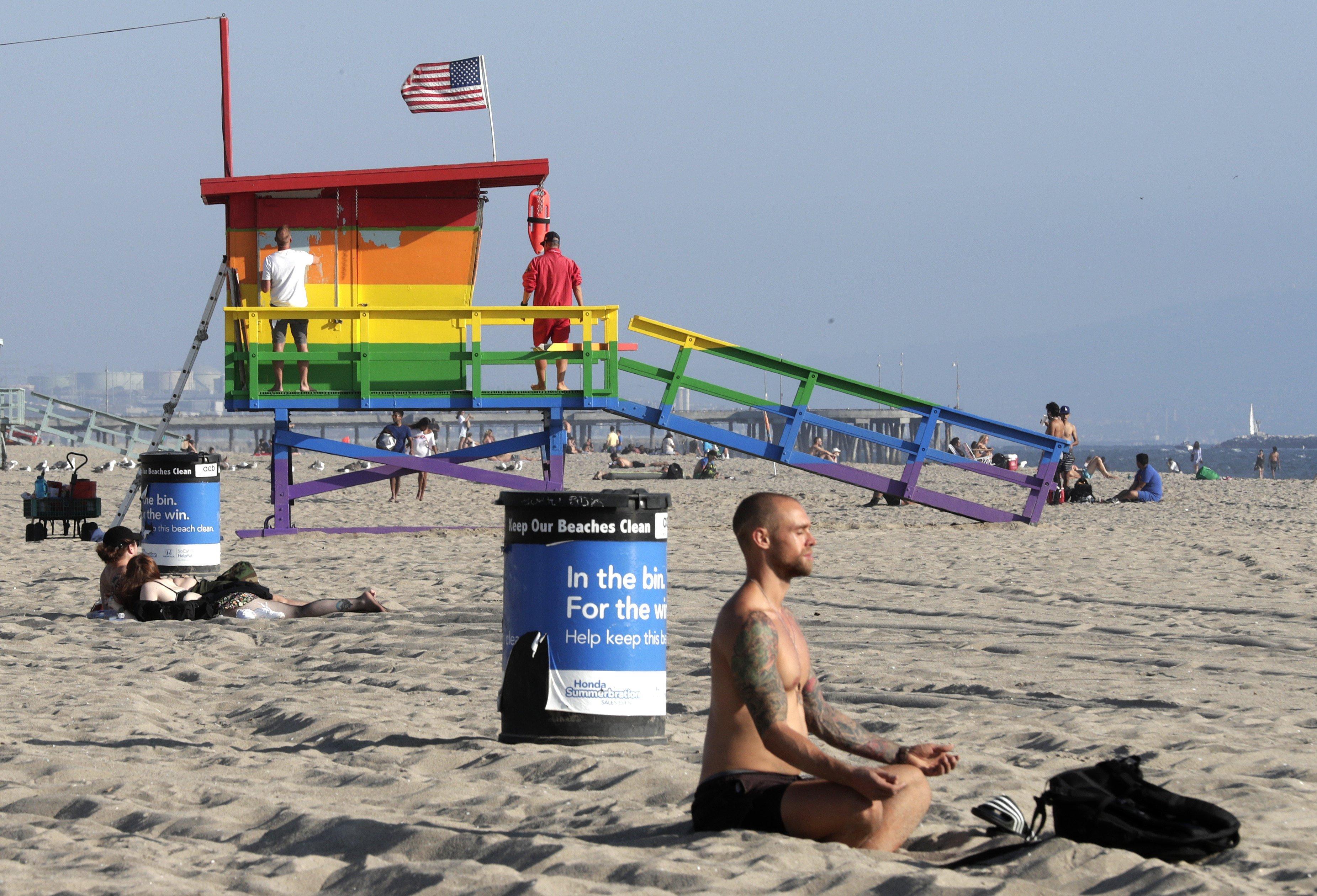 Un home medita al costat de la torre de socorrisme de l'orgull de Venècia, després que se li permetés romandre pintada amb els colors de la bandera de l'orgull de LGTBI. /MIKE NELSON