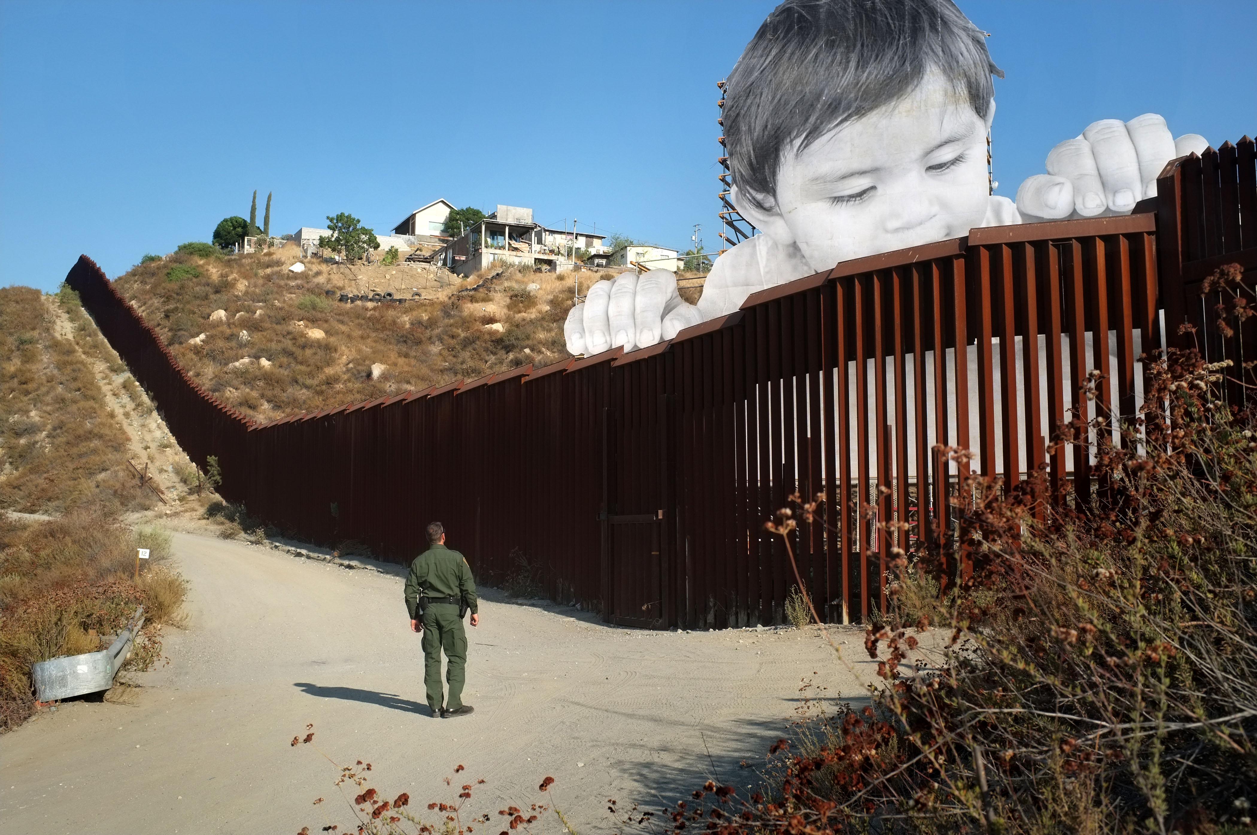 """Un agent de la Patrulla Fronterera nord-americana observa l'obra """"Kikito"""", de l'artista francès JR, que s'aixeca entre la frontera dels EUA i Mèxic. /DAVID MAUNG"""