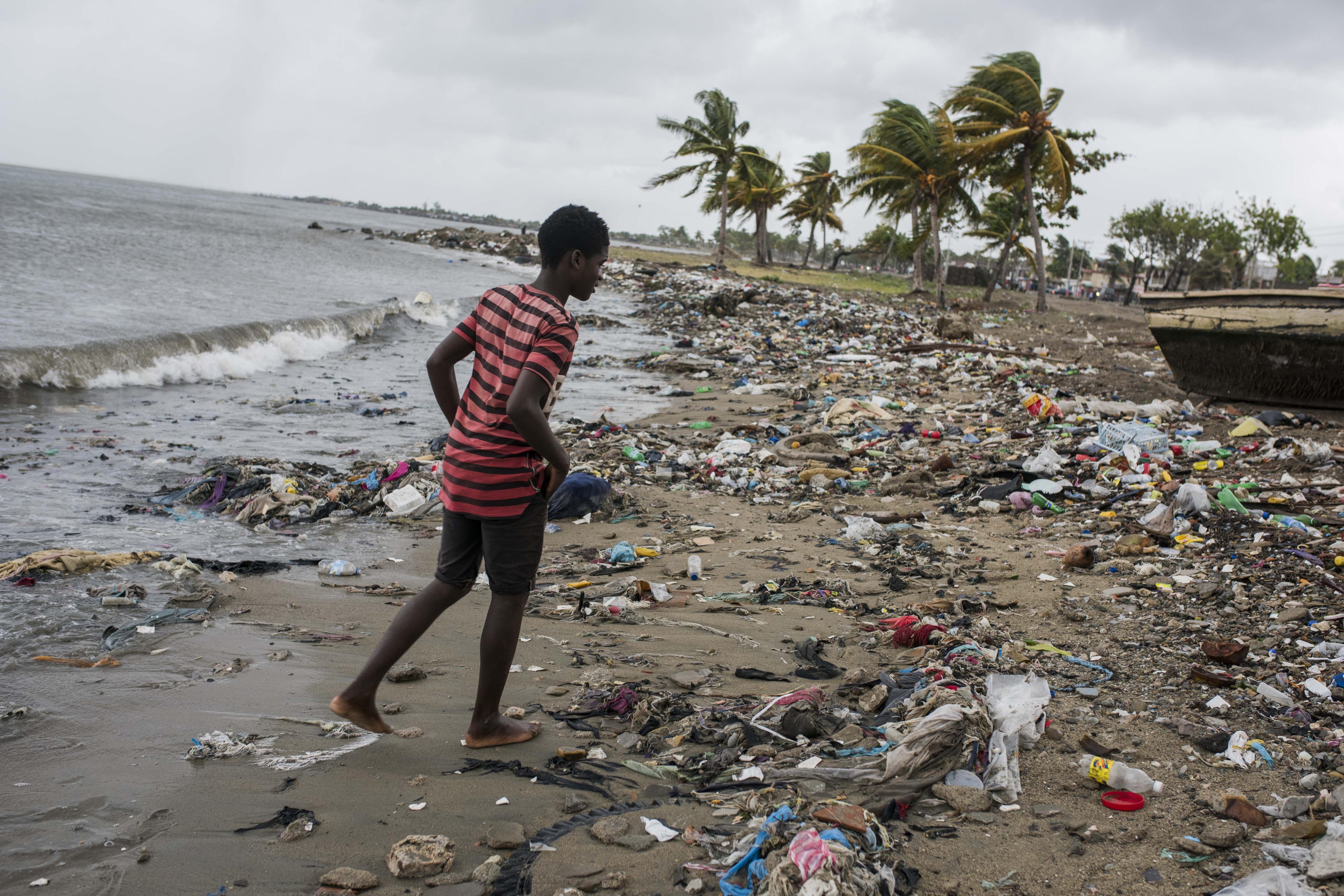 Un jove camina per la platja coberta de deixalles arrossegades pels forts vents durant el pas de l'huracà Irma per Haití. /JEAN MARC HERVE ABELARD