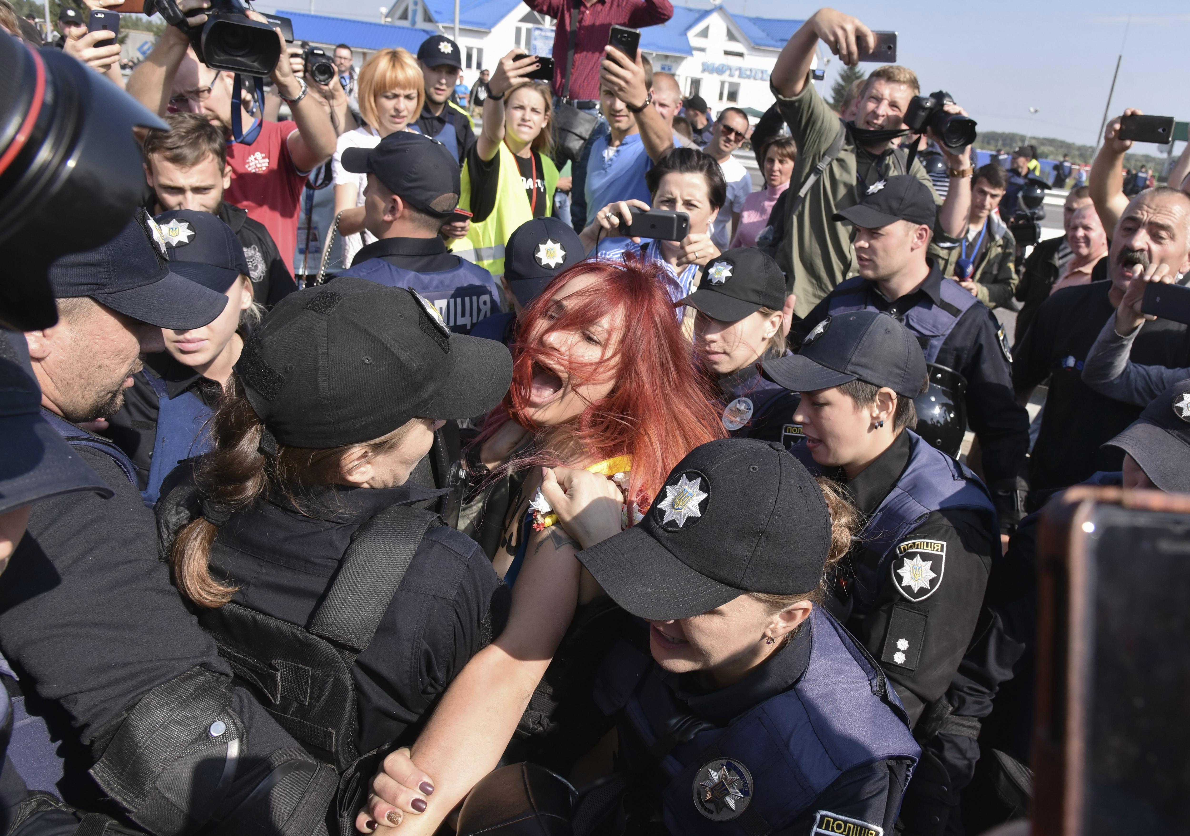 Els policies ucraïnesos detenen una activista en topless del moviment feminista Femen durant la seva protesta davant del pas de la frontera de Krakovets, Ucraïna. /MYKOLA TYS