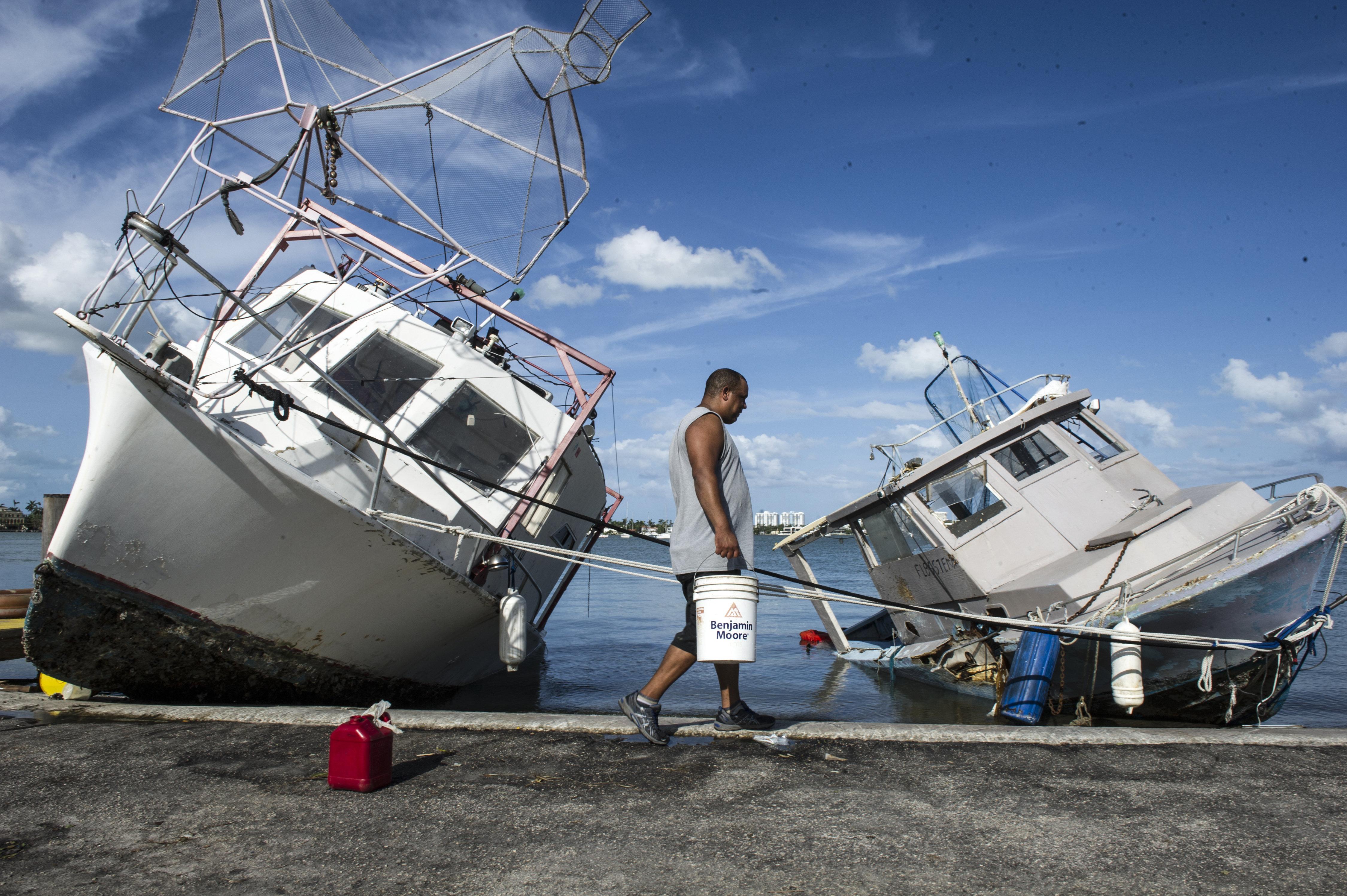 Jaime Prado camina enfront de dos vaixells encallats a la riba de Watson Island, a Miami Beach, Florida (EUA). /GIORGIO VIERA