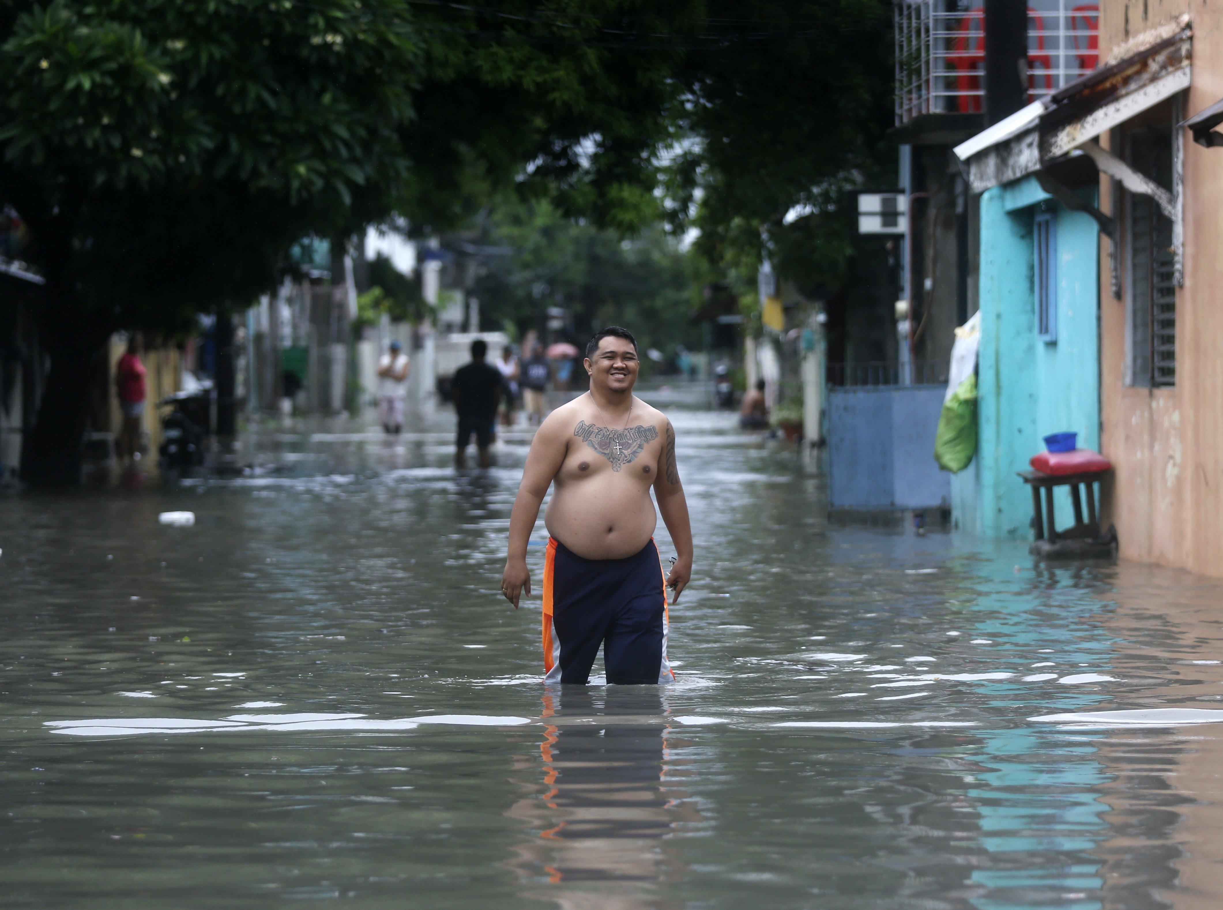 Filipins caminen pels carrers inundats al sud de Manila (Filipines). /FRANCIS R. MALASIG