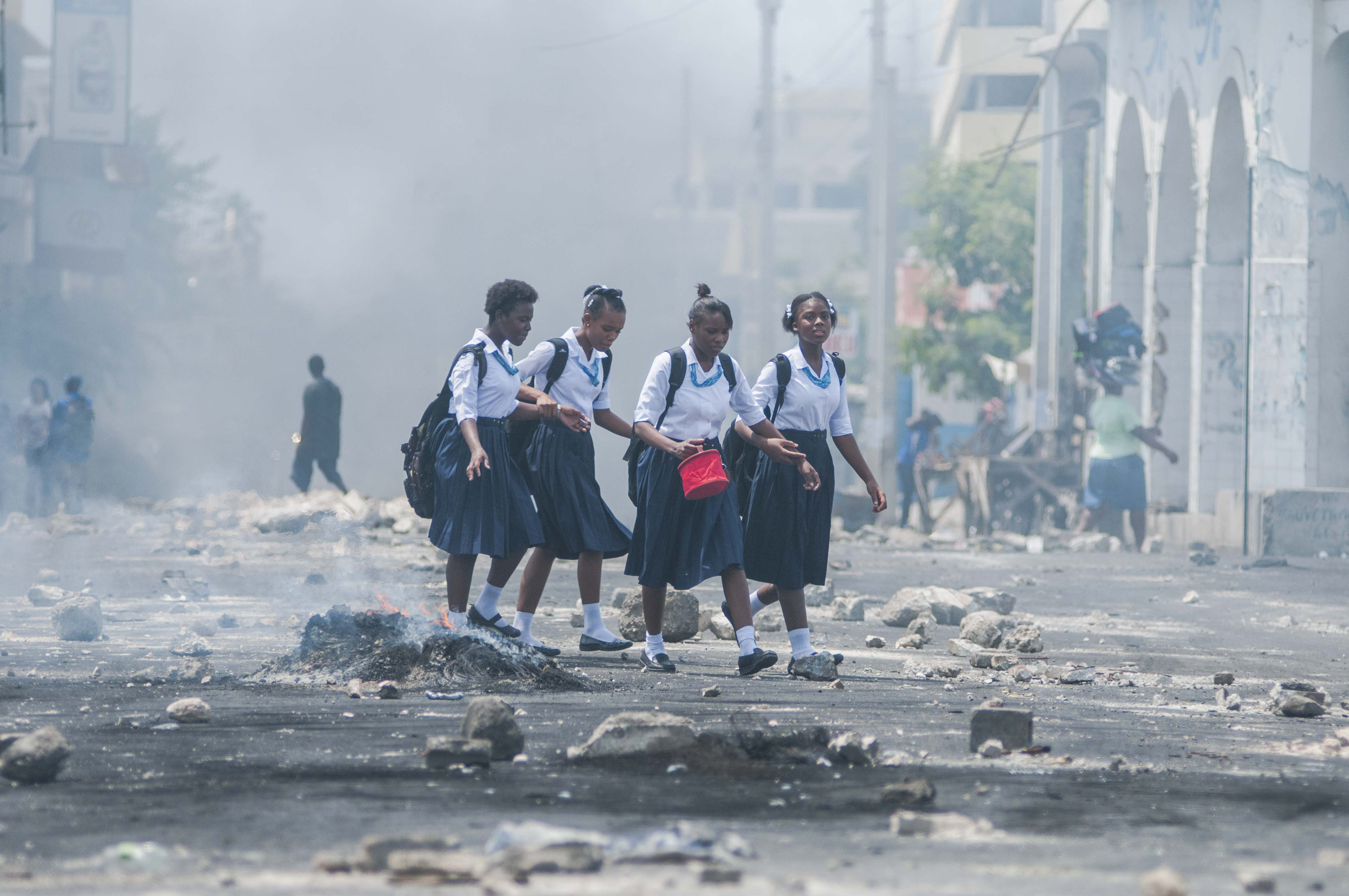 Nines en uniforme caminen pel carrer durant una manifestació a Haití contra l'aprovació per part del Parlament del Pressupost Nacional, en considerar que eleva els impostos de diversos serveis públics. /JEAN MARC HERVE ABELARD