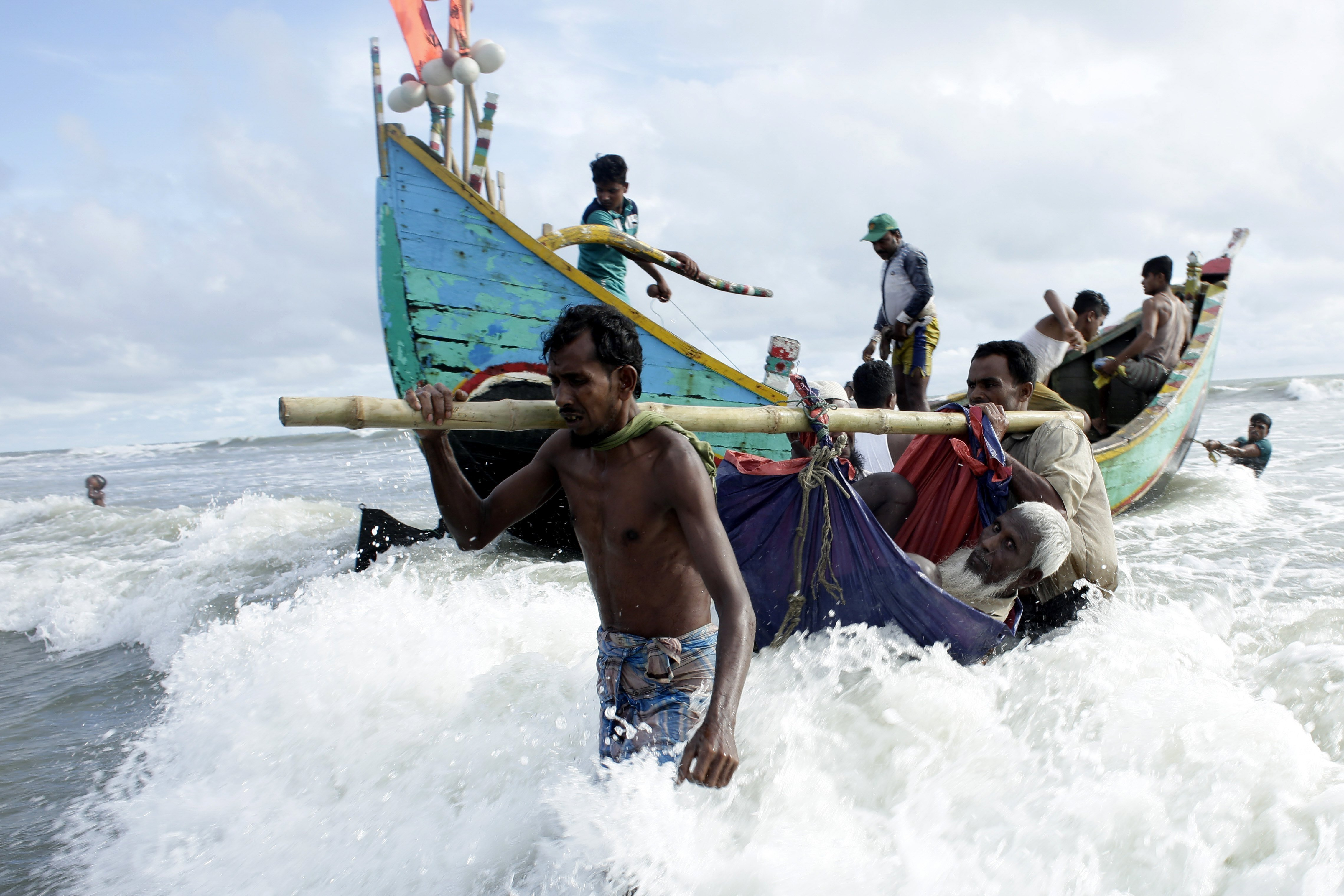 Refugiats rohinyàs transporten un home per la riba del riu Naf després de la seva arribada amb vaixell, a Teknaf, Bangladesh. /ABIR ABDULLAH