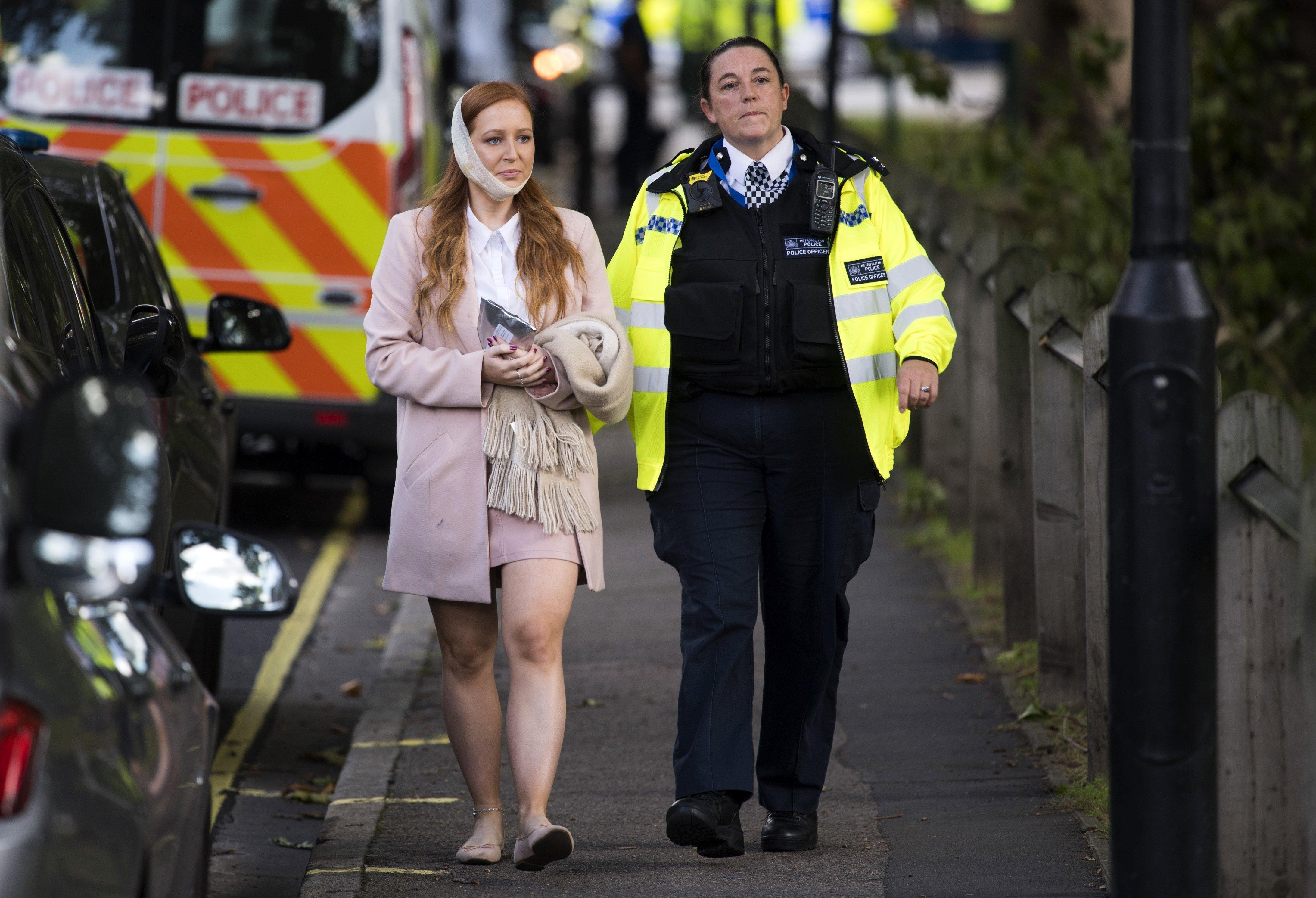 Una agent de policia escorta una ferida als voltants de l'estació de metro Parsons Green a Londres (Regne Unit). /WILL OLIVER