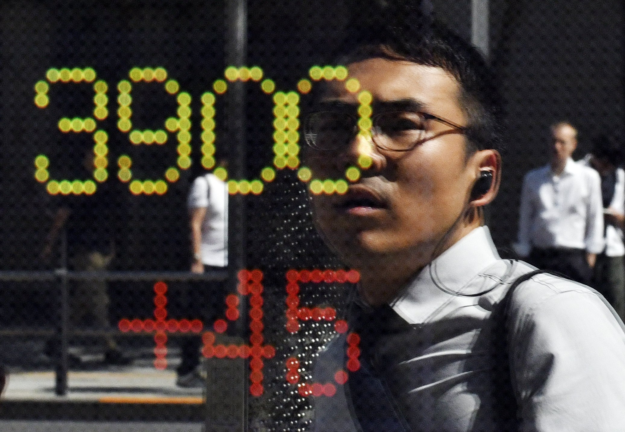 Un vianant es reflecteix en un indicador del mercat borsari a Tòquio. L'índex de referència Nikkei supera els 20.000 punts per primera vegada des de l'agost. /FRANCK ROBICHON