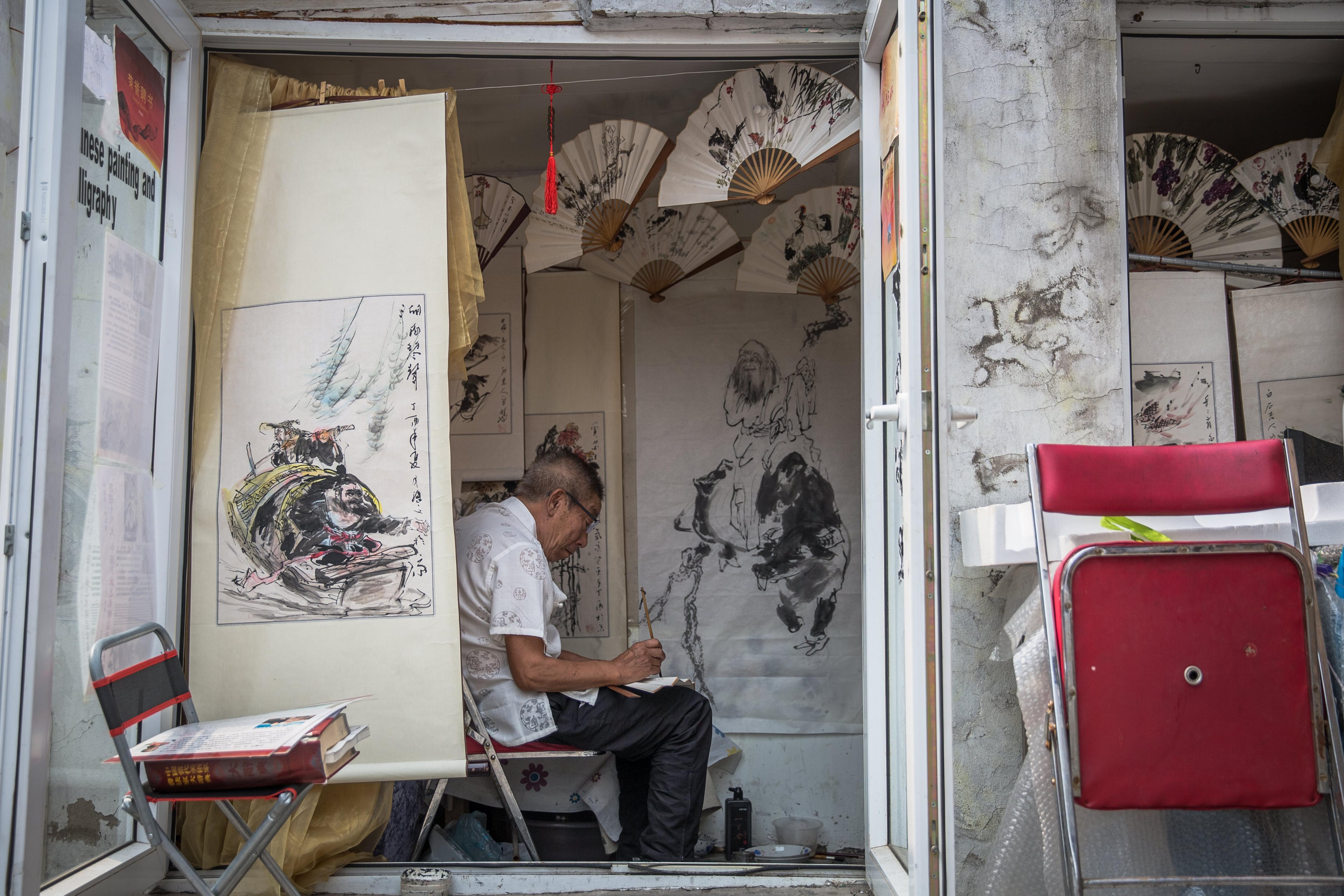 Un home pinta en el seu taller situat al barri Hutong de Pequín (Xina). /ROMAN PILIPEY
